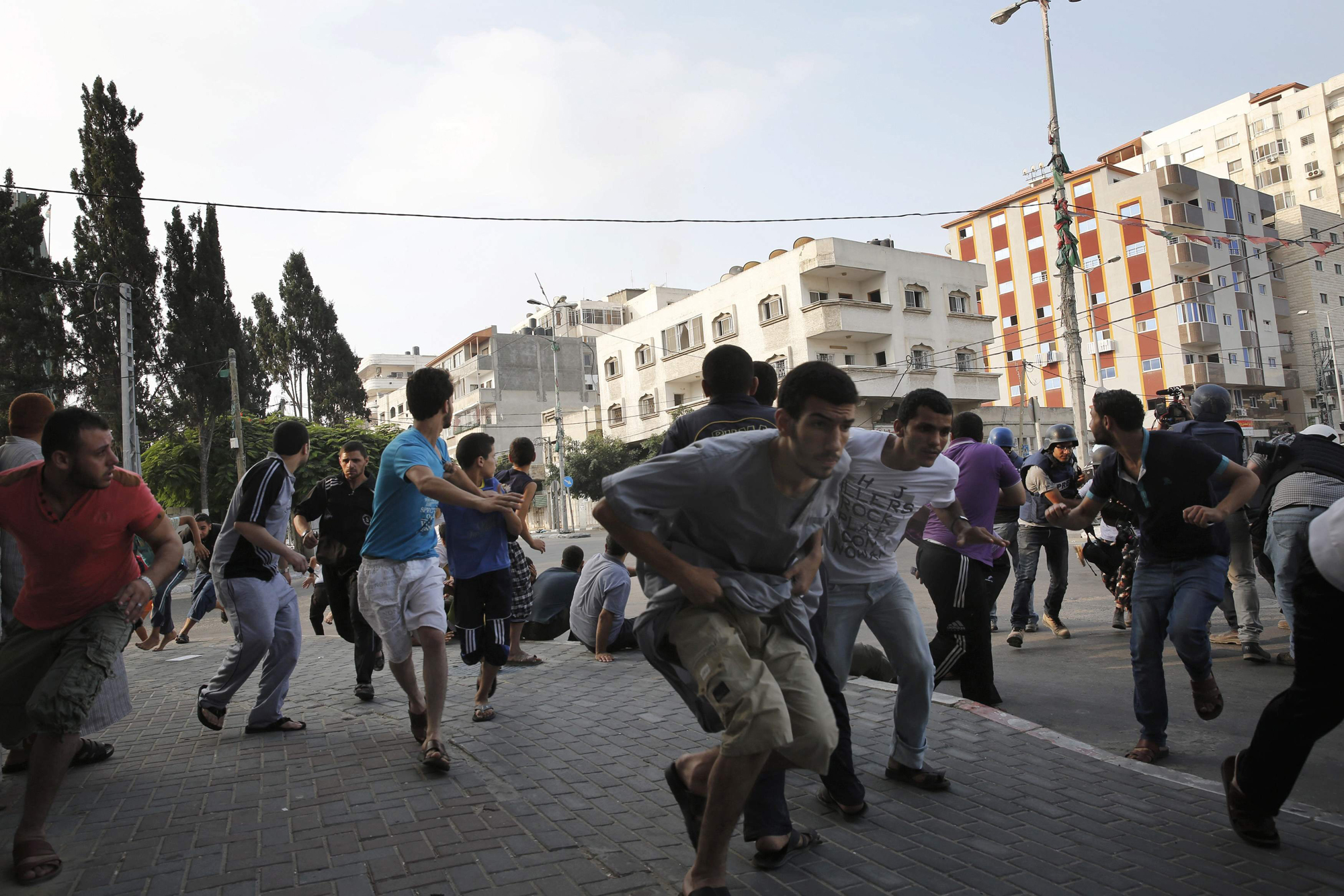 Palestinians take cover as warning Israeli air strikes are fired at a nearby building in Gaza City, July 22, 2014.