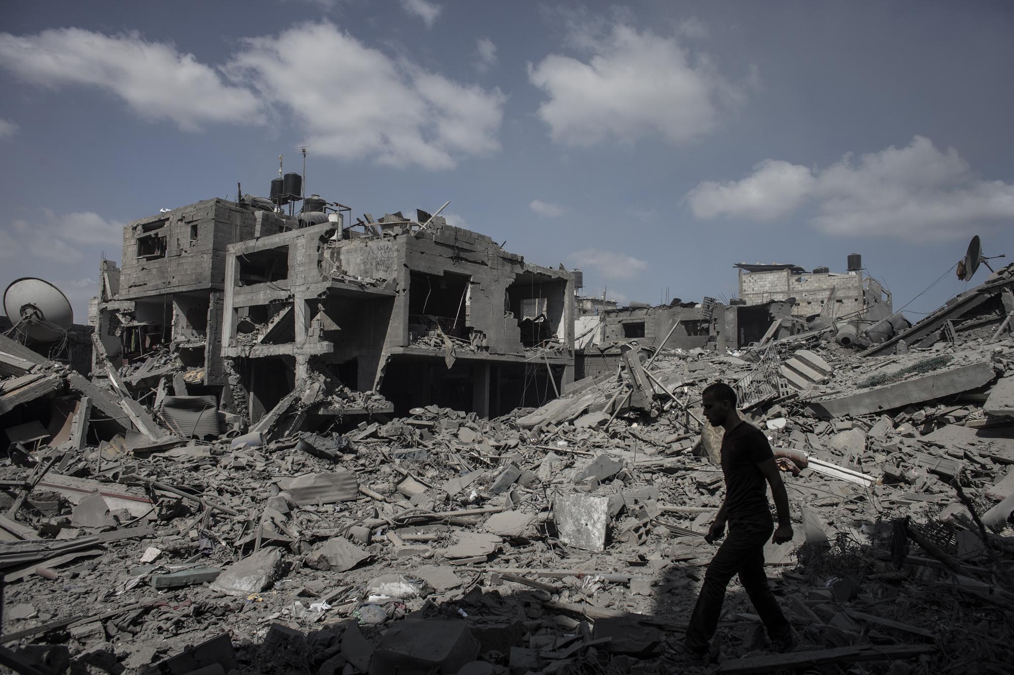 A Palestinian man walks past destroyed houses in Beit Hanoun, northern Gaza Strip, July 26 2014.