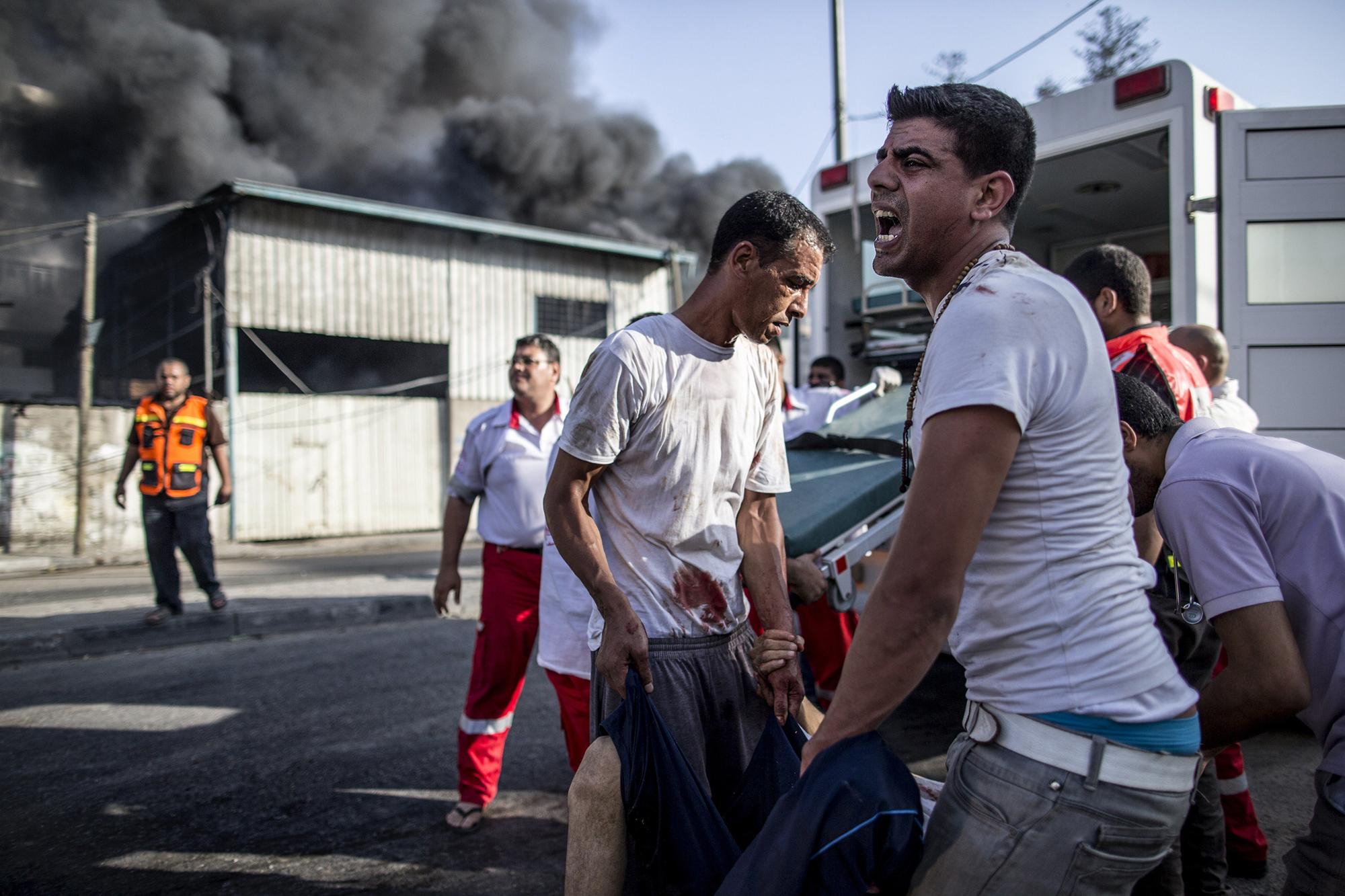 Palestinian emergency personnel and civilians evacuate victims of an Israeli air strike on a market place in the Shejaiya neighborhood near Gaza City, on July 30, 2014.