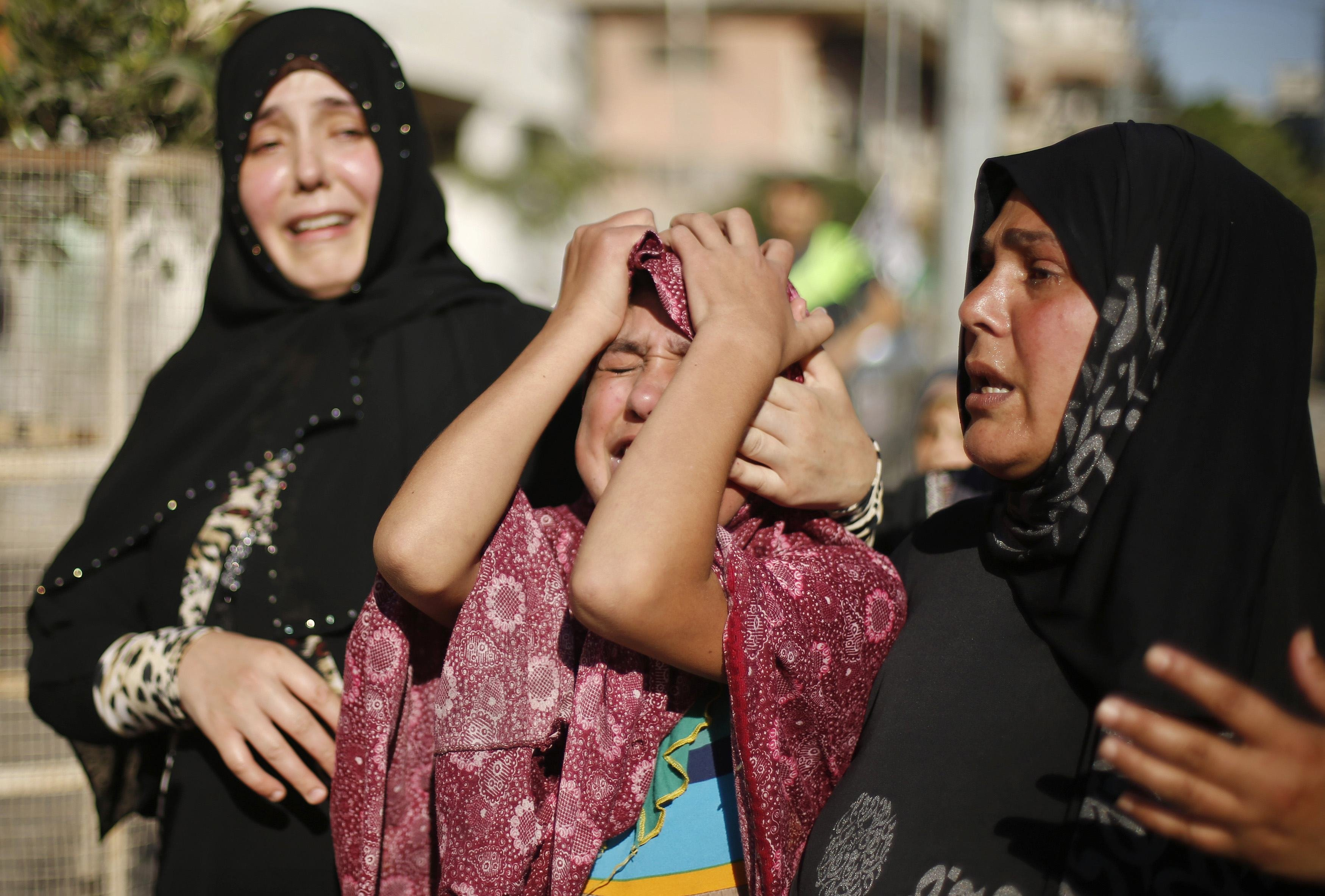 The sister (C) of a Palestinian boy from the Baker family, whom medics said was killed along with three other children from the same family by a shell fired by an Israeli naval gunboat, mourns during their funeral in Gaza City July 16, 2014.