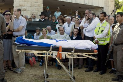 The parents of Naftali Frenkel, one of the three Israeli teens found dead, Rachel and Abraham sit in front of their son's body wrapped in an Israeli flag during his funeral service in their town of Nof Ayalon, Israel, July 1.