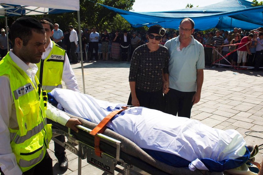 Bat-Galim and Ofir Shaer, parents of Gil-Ad, 16, one of three Israeli teens who were abducted and killed in the occupied West Bank, stand next to the Israeli flag-covered body of their son during a memorial service before his funeral, in the West Bank Jewish settlement of Talmon July 1.