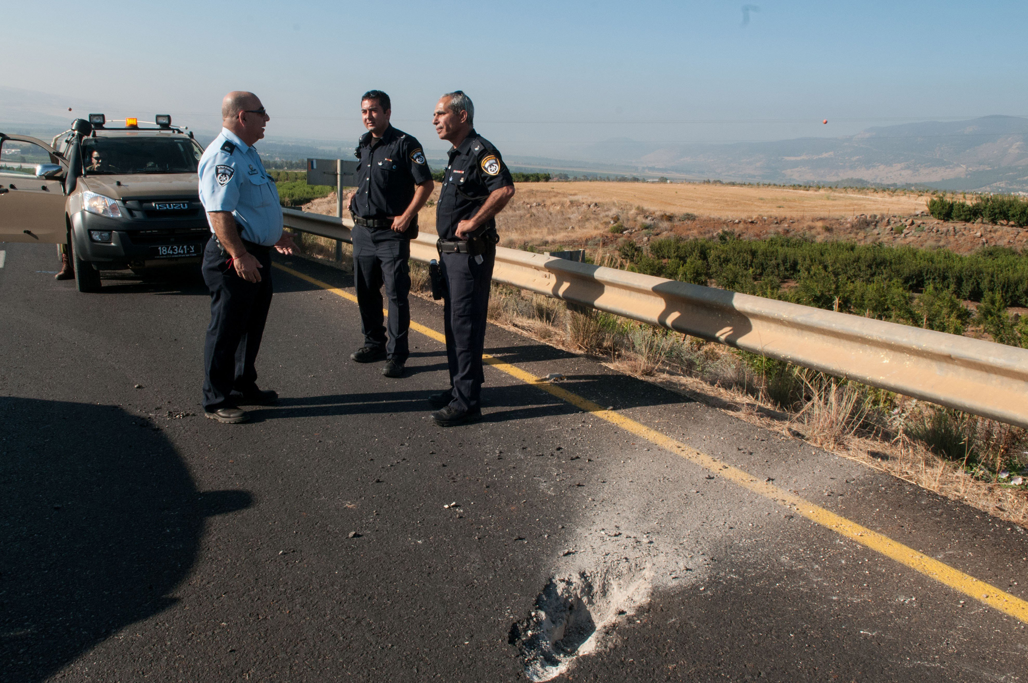 Israeli security forces stand next to damage caused by Katyusha style rocket fired from Lebanon near the border between northern Israel and Lebanon, on July 11, 2014.