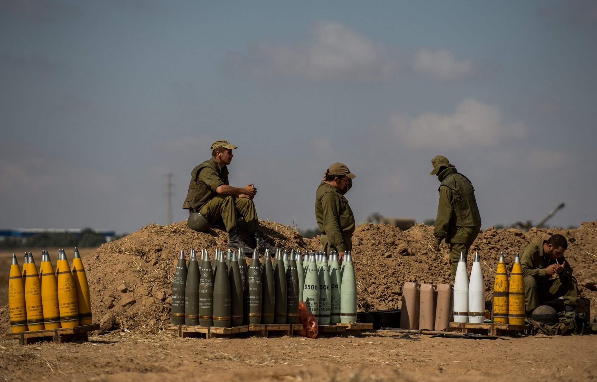 Israeli soldiers rest beside shells for a 155mm M109 Dores self-propelled howitzer at a position in Southern Israel near the border with Gaza, on the seventh day of Operation Protective Edge, on July 14, 2014.