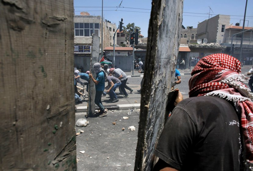Palestinian stone-throwers take cover during clashes with Israeli police in Shuafat, an Arab suburb of Jerusalem, July 2.