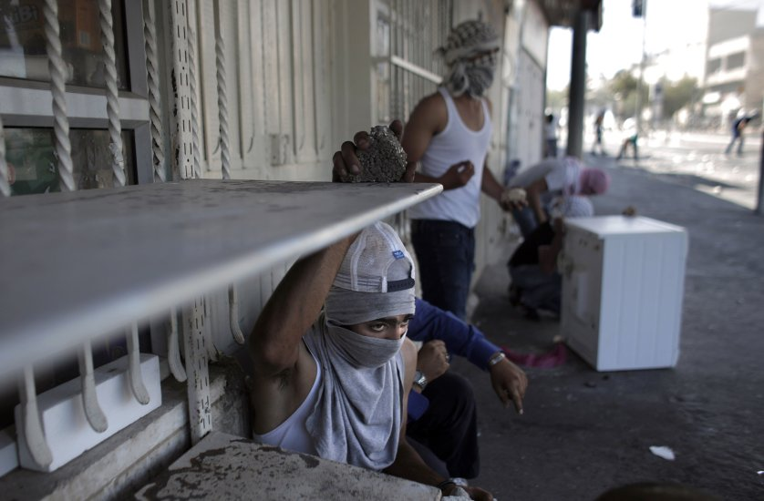 Masked Palestinian protestors take cover as they throw stones toward Israeli police during clashes in Shuafat suburb of Jerusalem, on July 2.