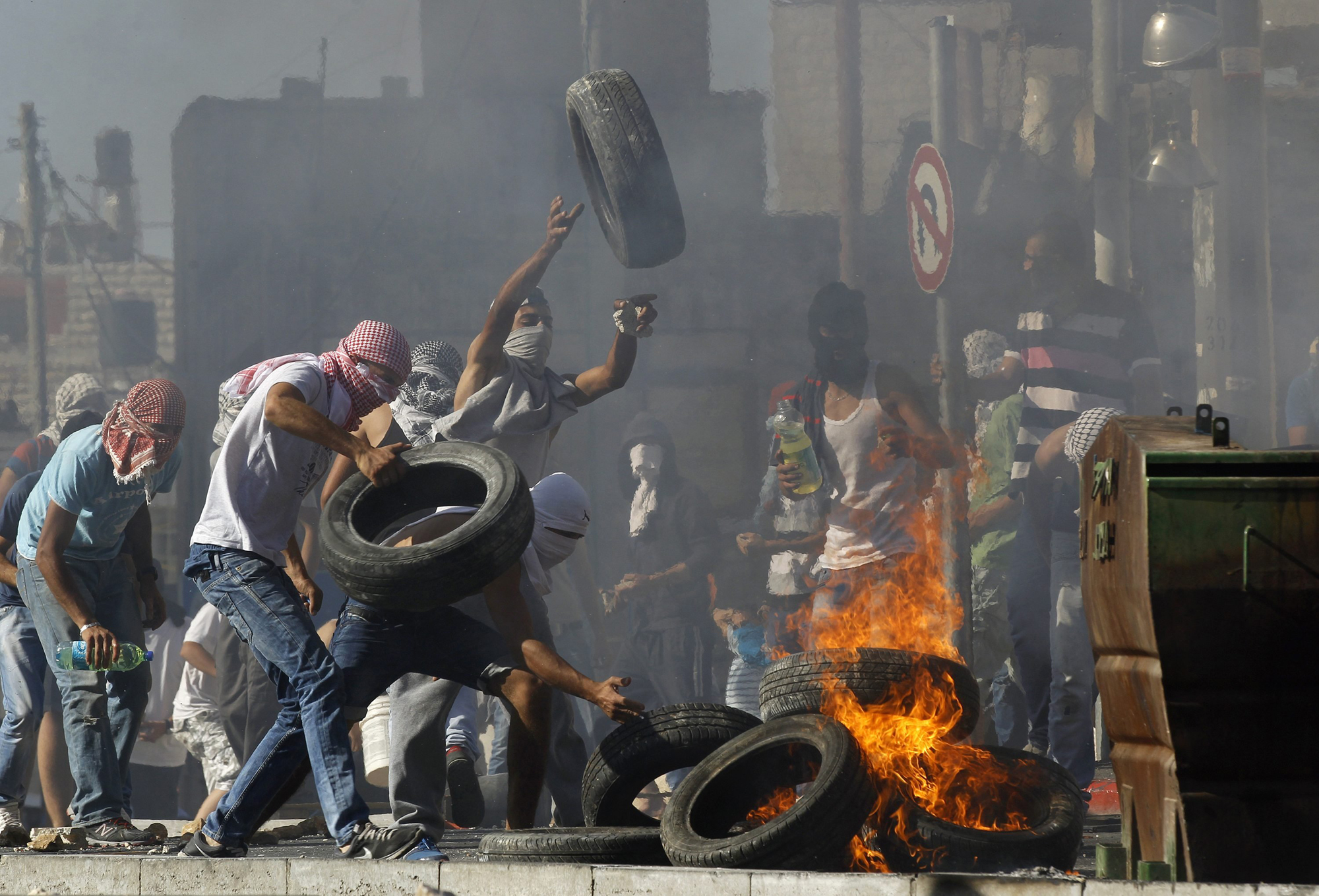 Palestinians set tyres ablaze during clashes with Israeli police in Shuafat, an Arab suburb of Jerusalem July 2.