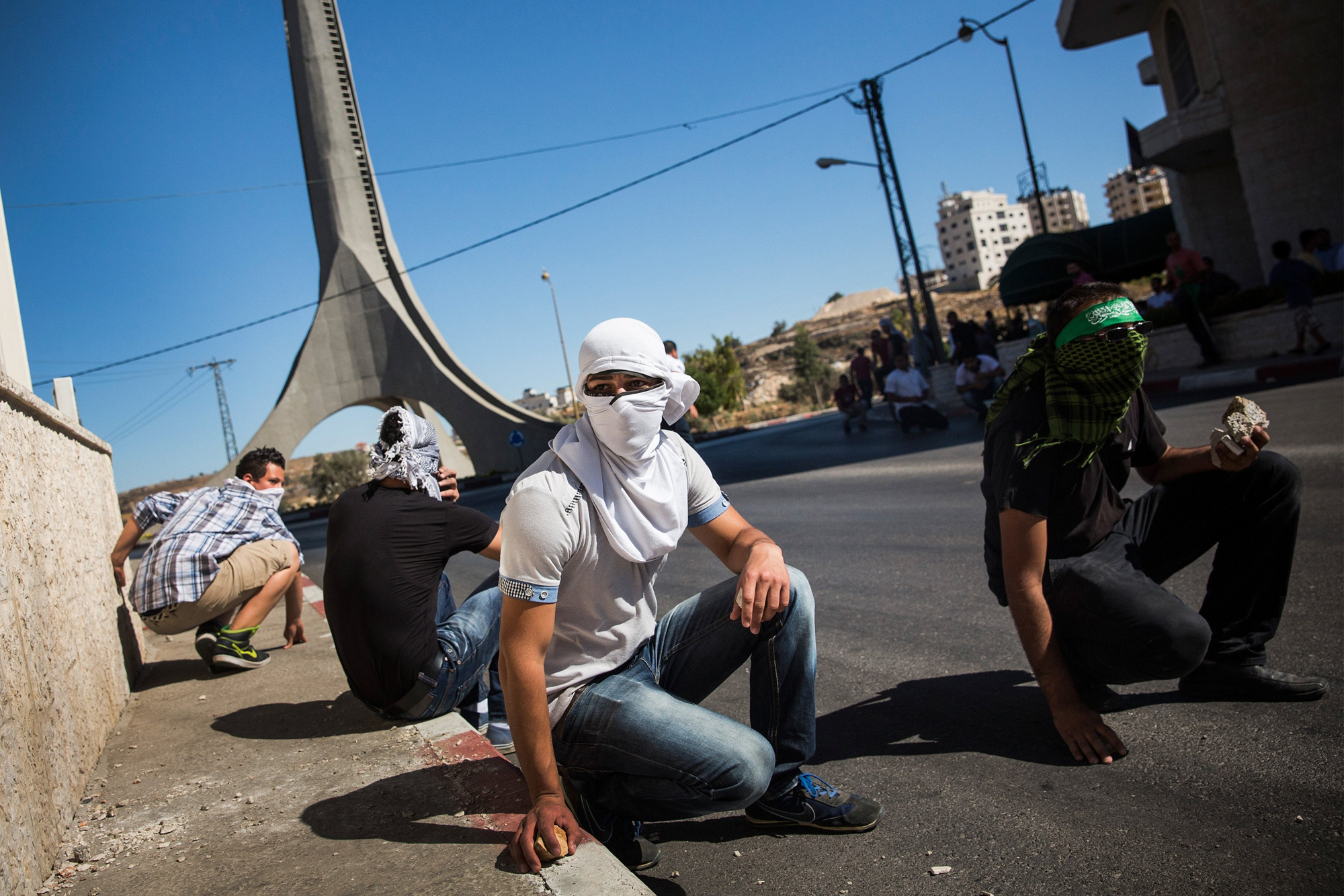Palestinian supporters of Hamas take shelter while clashing with Israeli security forces on July 25, 2014 near Ramallah, West Bank.