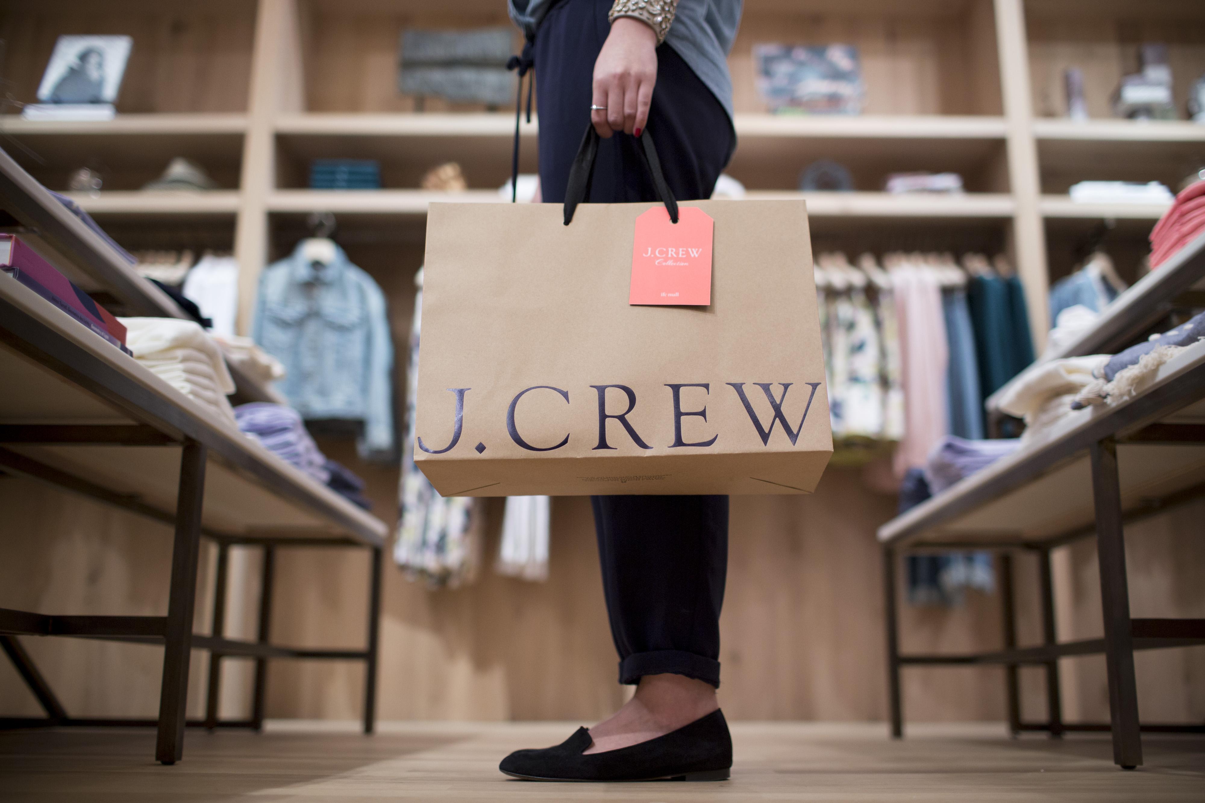 A women holds a J. Crew shopping bag.
