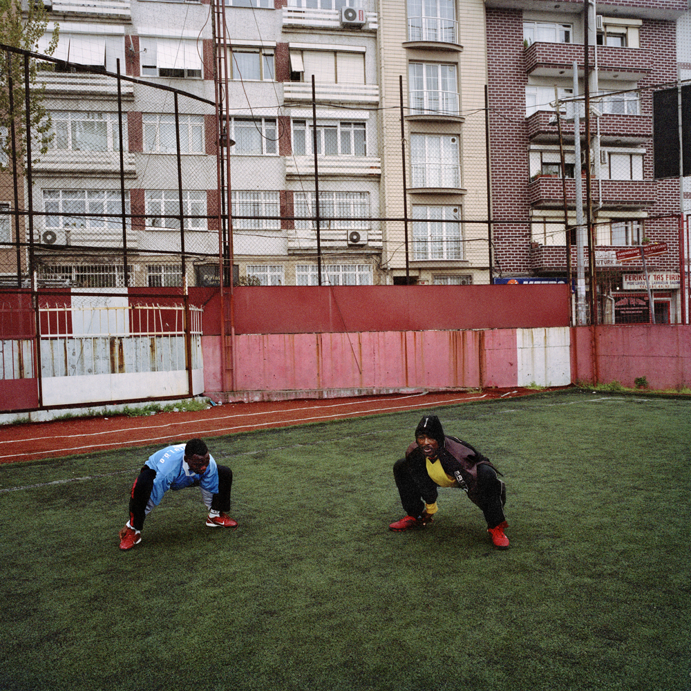 Sodiq and Adegeye, two Nigerian soccer players living in Istanbul, stretch during an early evening practice on the rundown Feriköy pitch in April 2011 in the Kurtulus neighborhood of Istanbul.