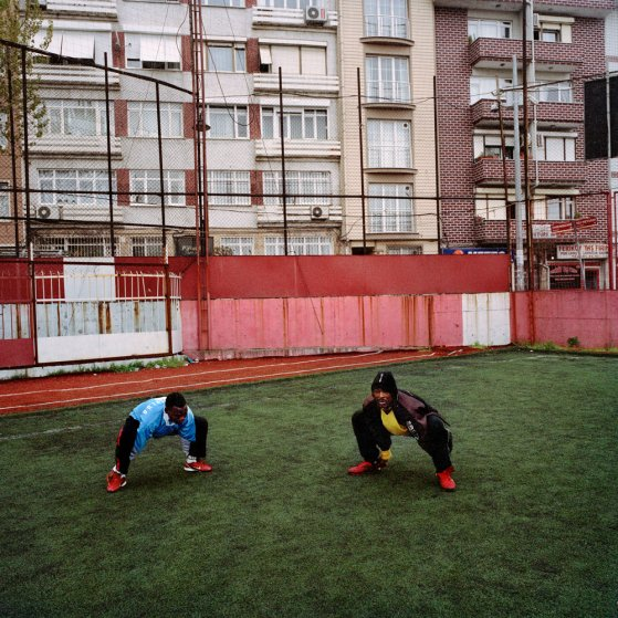 Sodiq and Adegeye, two Nigerian footballers living in Istanbul, stretch during an early evening practice on the rundown Feriköy pitch in April 2011 in the Kurtulus neighborhood of Istanbul, Turkey.