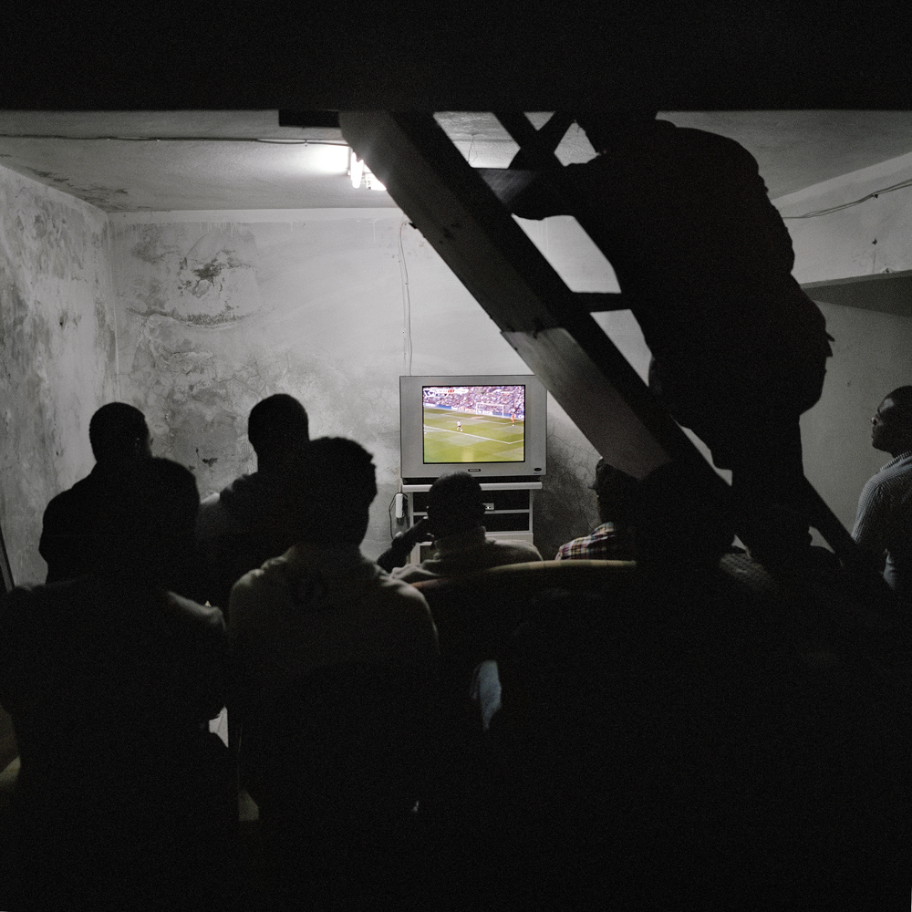 A group of African men crowd the basement of an Internet cafe to watch the Chelsea vs. Tottenham soccer match after paying the shop keeper 50 cents on April 30, 2011 in the Kurtulus neighborhood of Istanbul.