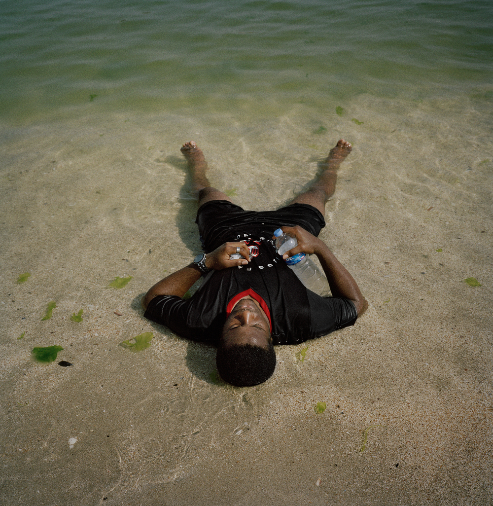 Jerry, a Nigerian soccer player, lays in the sea at a beach near his home after spending the afternoon training in August 2011 in Istanbul.