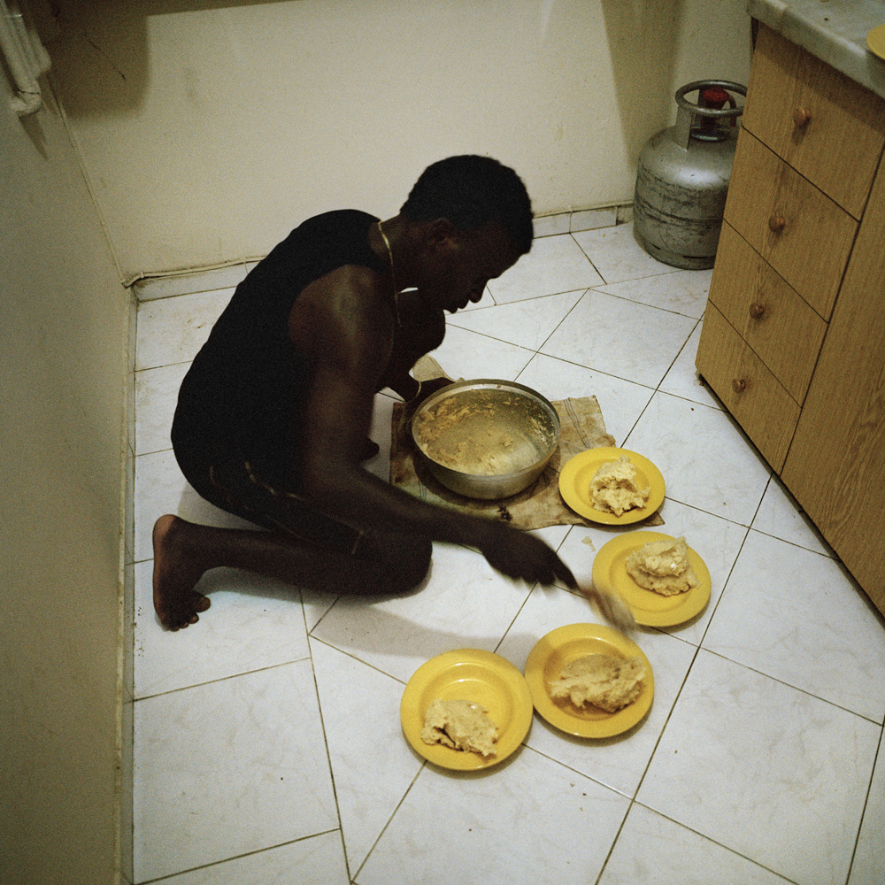 Akeem, a Nigerian soccer player, prepares Banku; a Ghanian staple dish that's traditionally served with stew, on the floor of the apartment that he shares with seven other Nigerians inside the three room apartment located in the basement of a building in March 2013 in the Sisli neighborhood  of Istanbul.