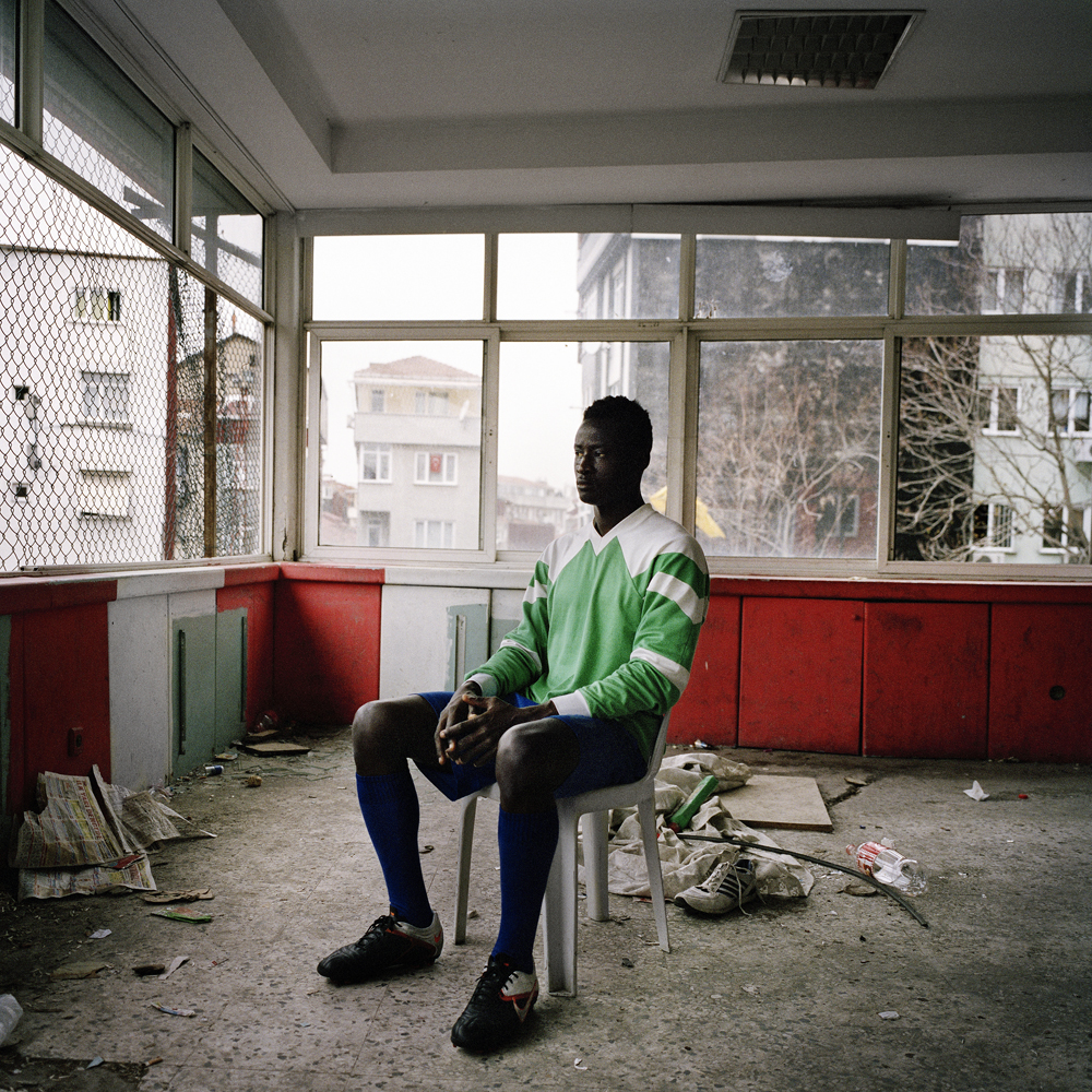 Dayo, a Nigerian soccer player living in Turkey, sits for a portrait inside the second floor of the run-down Feriköy Pitch in Istanbul where he trains five days a week in April 2013 in Istanbul.