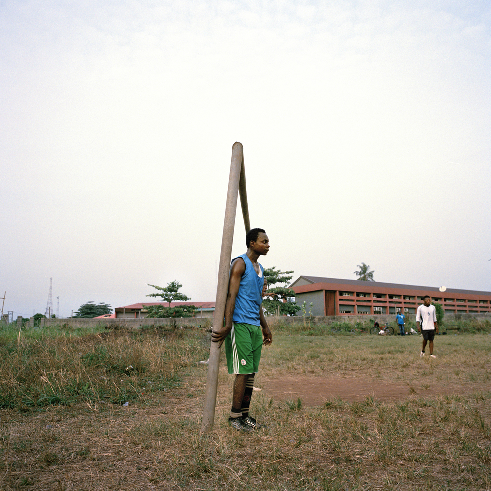 Peter, a soccer player with two children and a wife, holds onto the goal post during an afternoon practice at the Government Technical College in February 2014 in Ikorodu, Nigeria.
