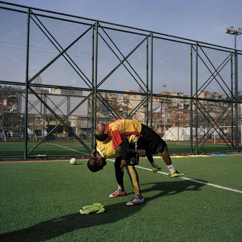 Two Nigerian soccer players stretch during a morning workout for SIBM LTDA, a training program run by Sevgi Adar, a Cameroonian agent based in Turkey in January 2014 in Istanbul.