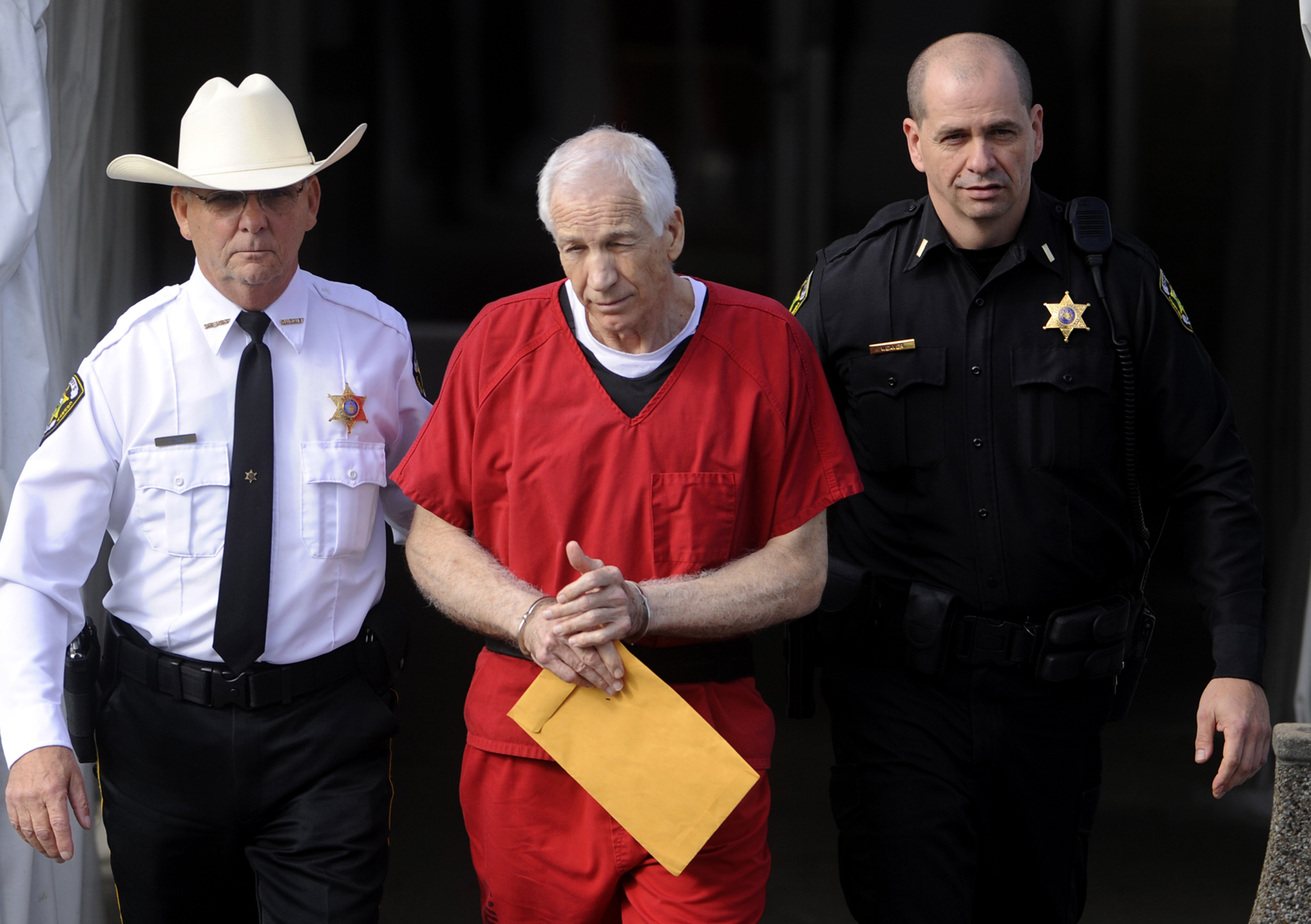 Jerry Sandusky, center, is escorted from his sentencing at the Centre County Courthouse in Bellefonte on Tuesday, October 9, 2012.
