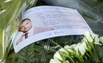 A bunch of flowers with a picture and a message for John Allen, a British lawyer who died with his Dutch wife and three sons on flight MH17, is placed at Schiphol airport, in Amsterdam, July 20, 2014.