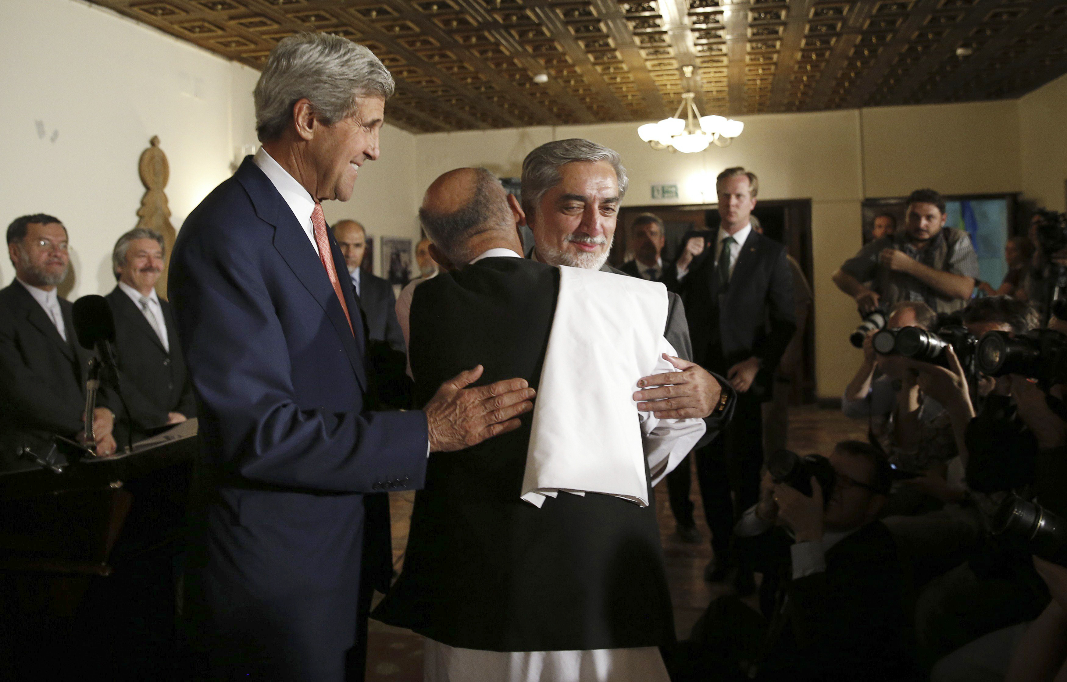 Presidential candidates Abdullah Abdullah, right, and Ashraf Ghani embrace at a news conference with Secretary of State John Kerry where a deal to audit ballots was announced, in Kabul, Afghanistan on July 12, 2014.