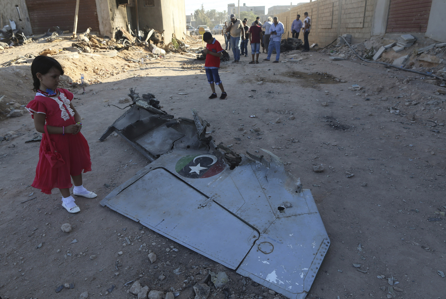 A Libyan girl stands next to the wreckage of a government MiG warplane that crashed during clashes in Benghazi, Libya, on July 29, 2014