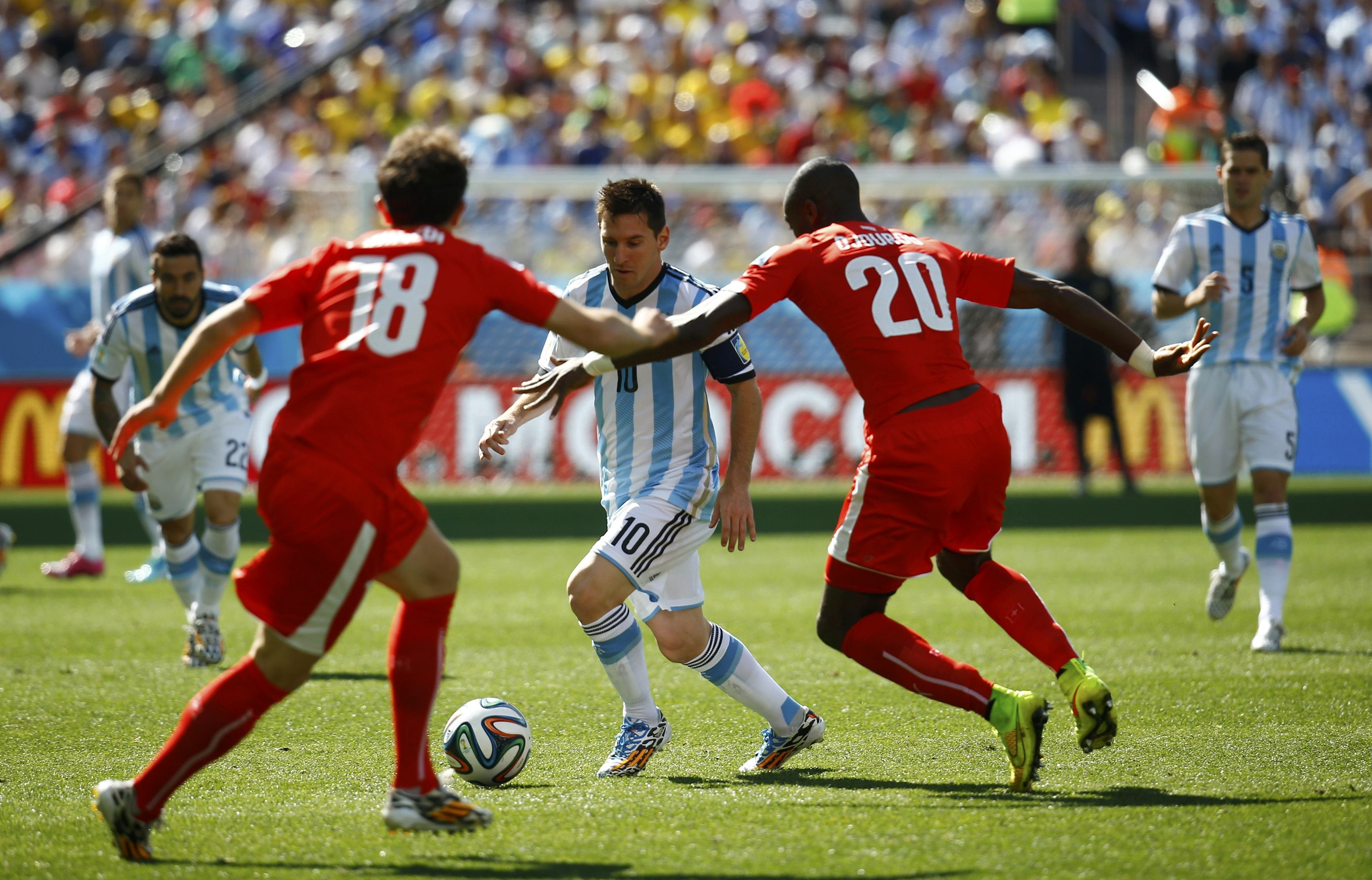 Argentina's Lionel Messi  fights for the ball with Switzerland's Admir Mehmedi and Johan Djourou during their 2014 World Cup round of 16 game at the Corinthians arena in Sao Paulo, Brazil on July 1, 2014.