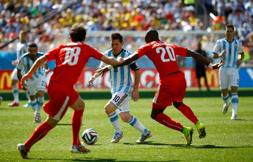 Argentina's Messi fights for the ball with Switzerland's Mehmedi and Djourou during their 2014 World Cup round of 16 game at the Corinthians arena in Sao Paulo