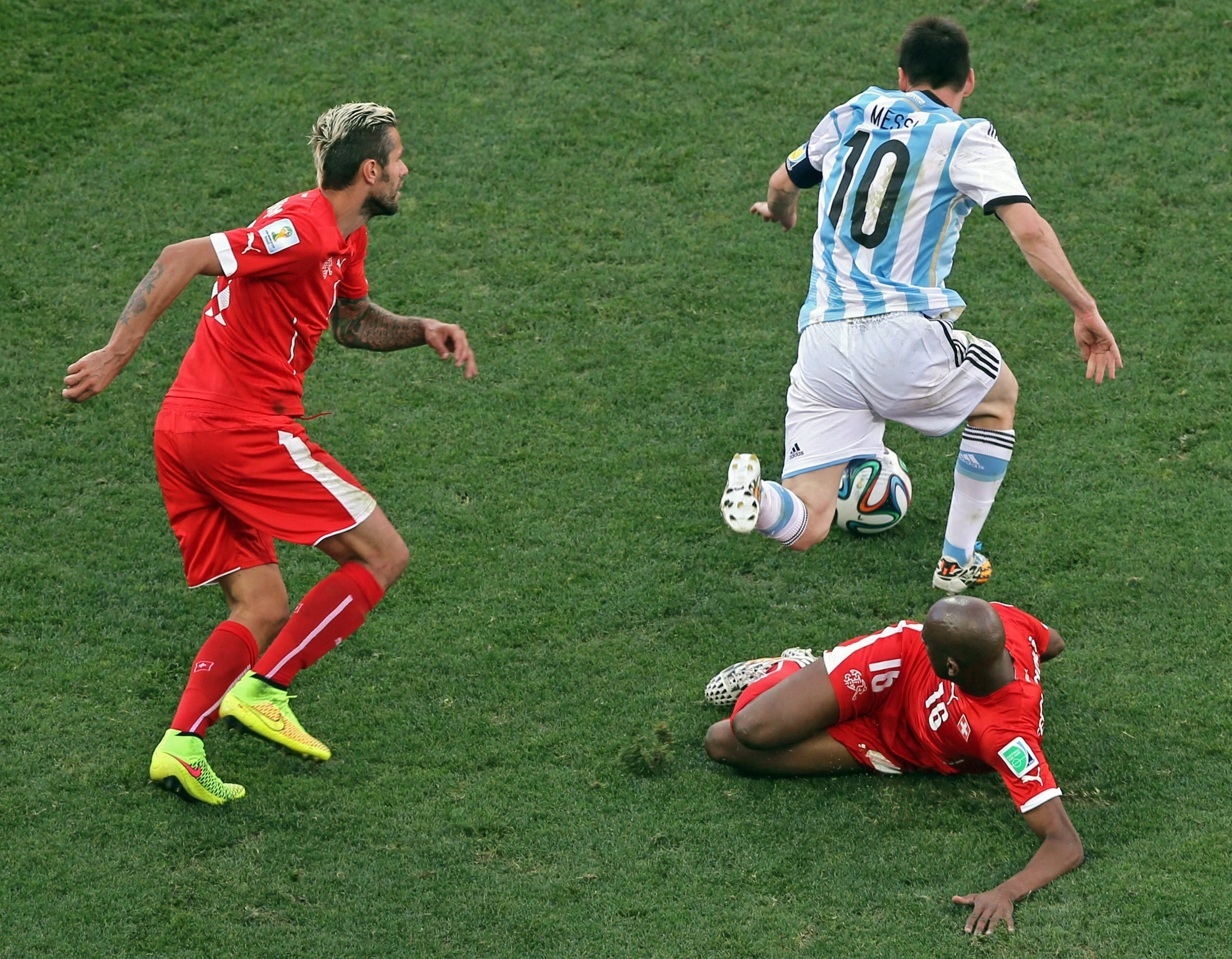 Argentina's Lionel Messi escapes from Switzerland's Valon Behrami (L) and Gelson Fernandes (R) during the FIFA World Cup 2014 round of 16 match between Argentina and Switzerland at the Arena Corinthians in Sao Paulo, Brazil, on July 1, 2014.