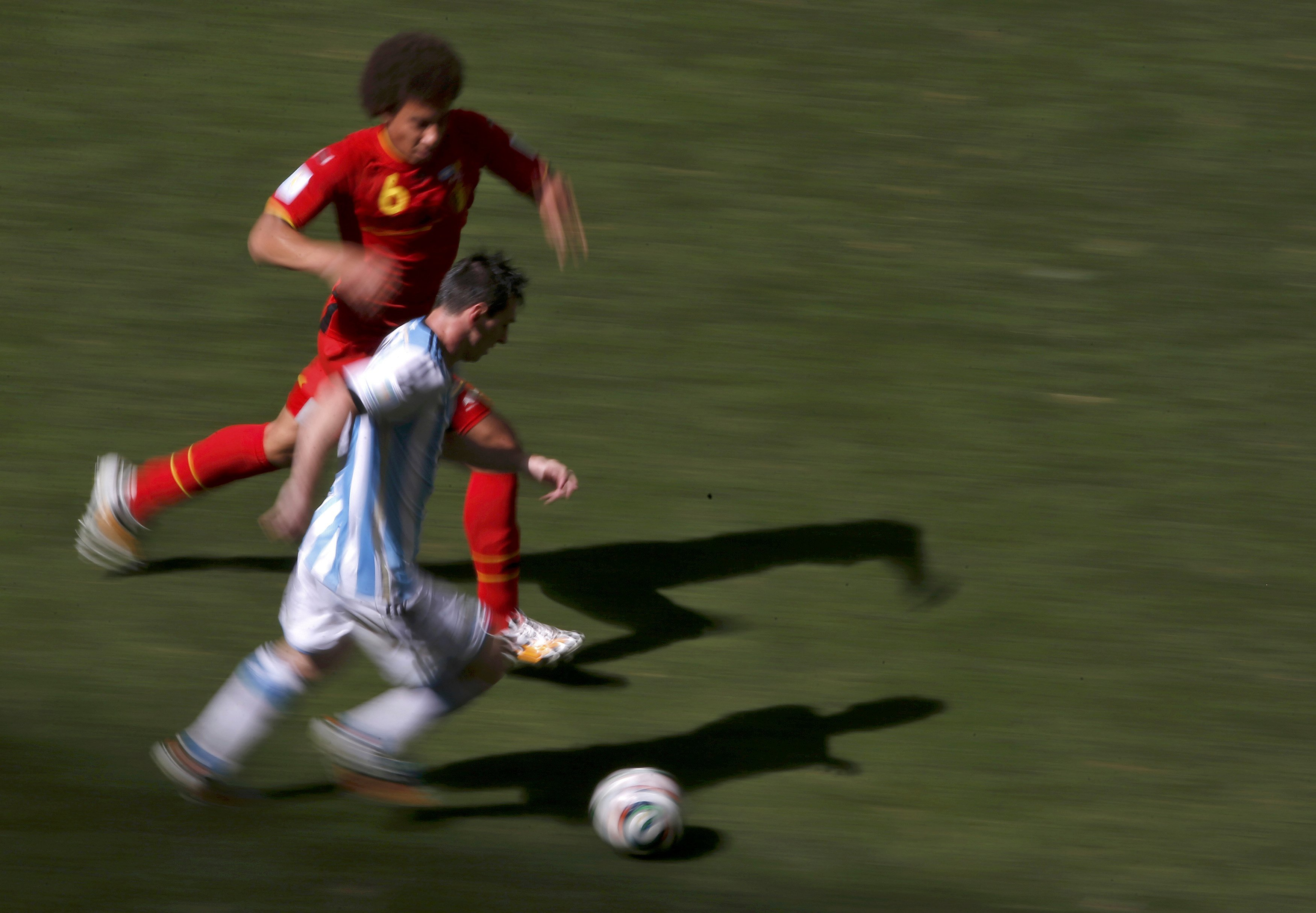 Argentina's Lionel Messi chases the ball with Belgium's Axel Witsel during their 2014 World Cup quarter-finals at the Brasilia national stadium in Brasilia on July 5, 2014.