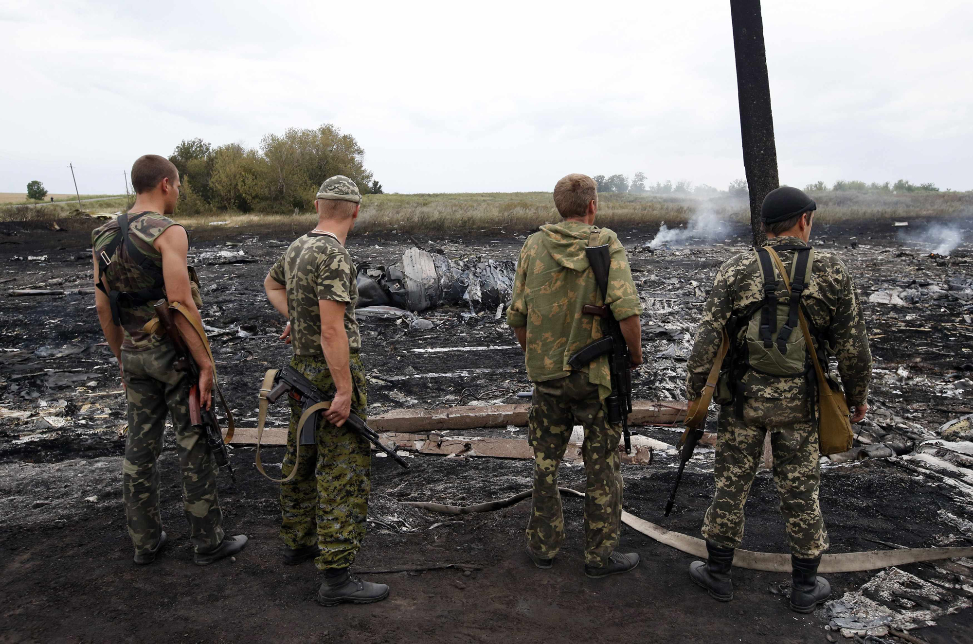 Armed pro-Russian separatists stand at the site of a Malaysia Airlines Boeing 777 plane crash near the settlement of Grabovo in the Donetsk region, July 17, 2014.