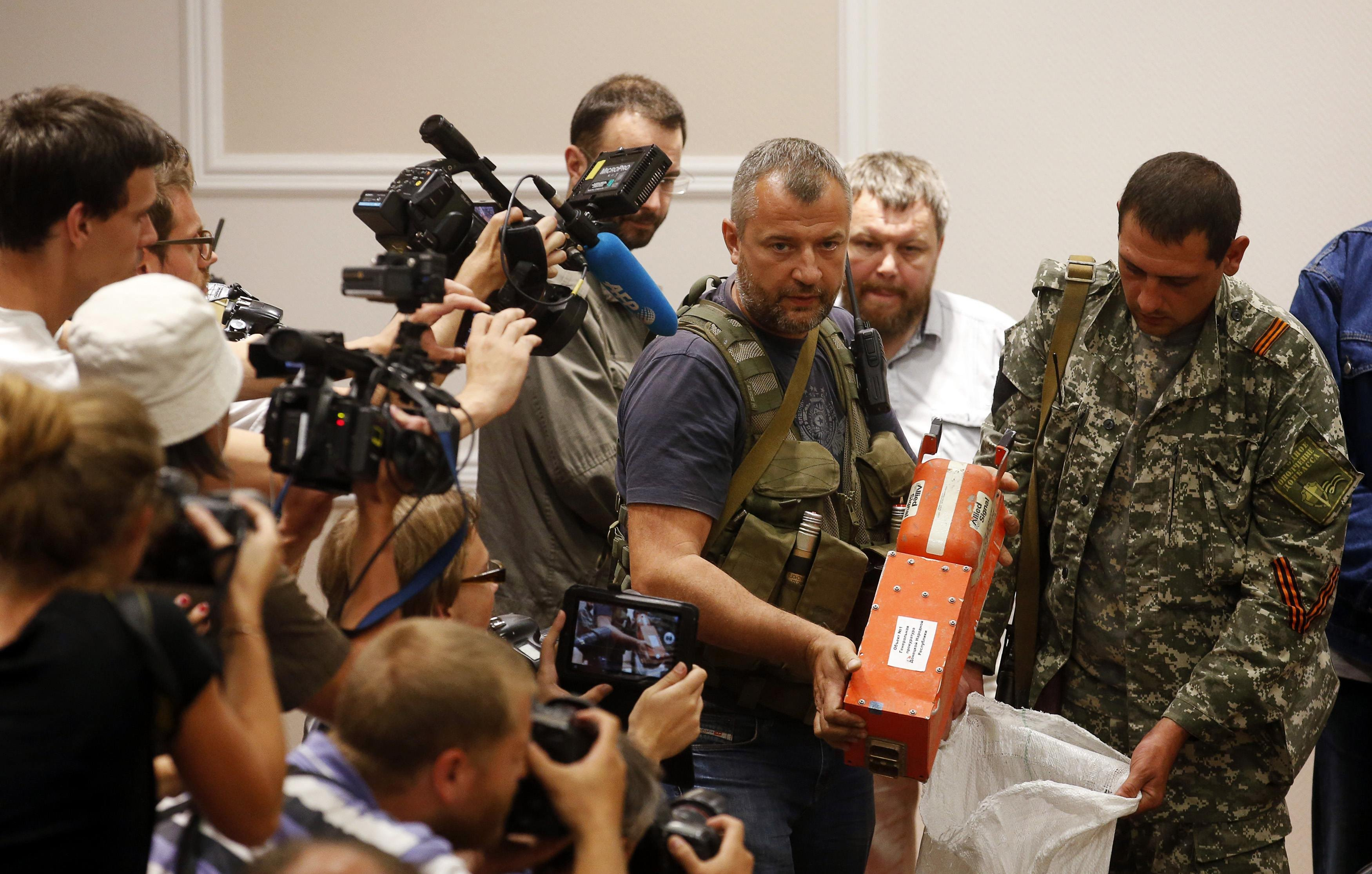 A pro-Russian separatist shows members of the media a black box belonging to Malaysia Airlines flight MH17, before its handover to Malaysian representatives, in Donetsk on July 22, 2014.