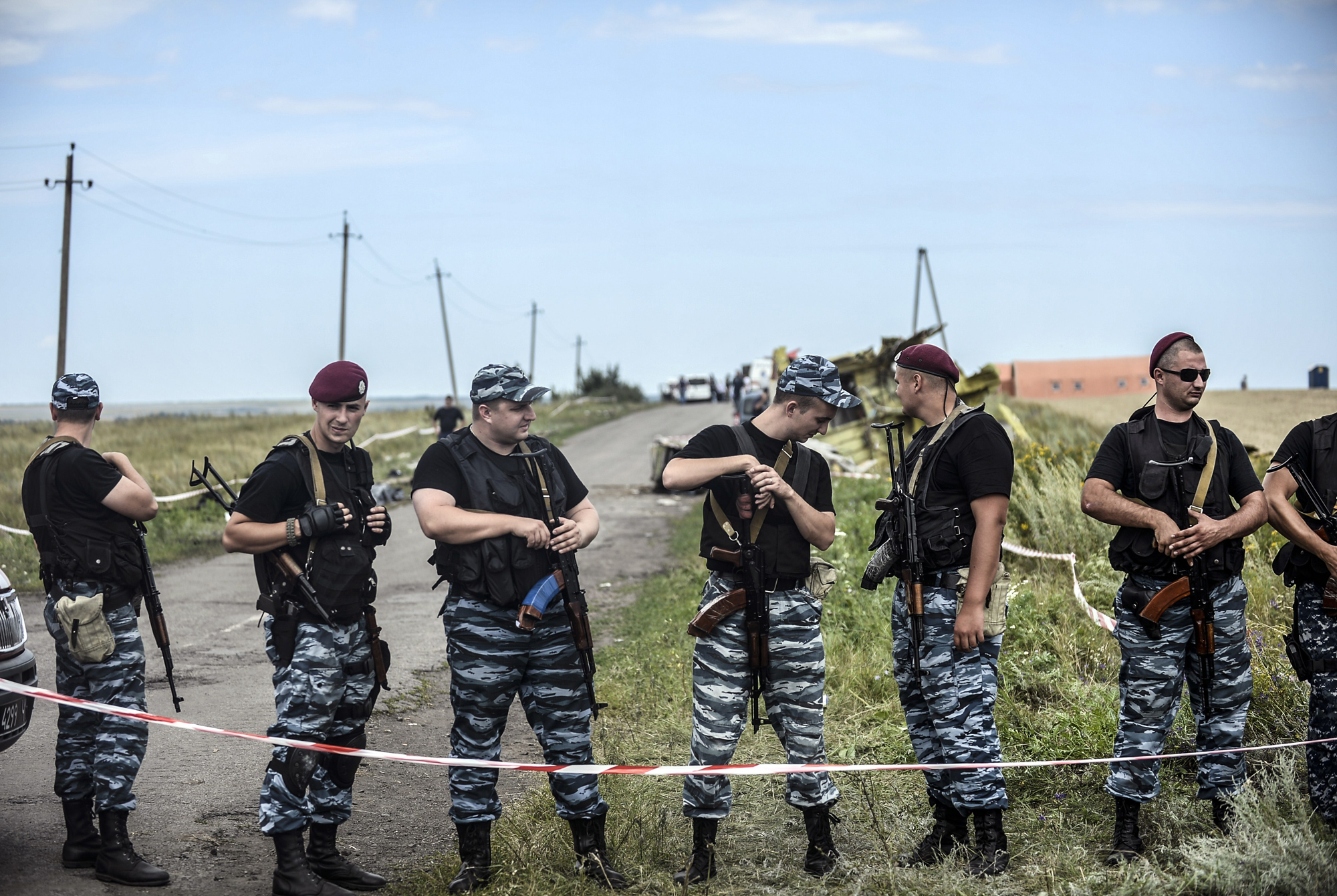 Armed pro-Russian separatists stand guard in front of the crash site of Malaysia Airlines Flight MH17, near the village of Grabove, in the region of Donetsk on July 20, 2014.