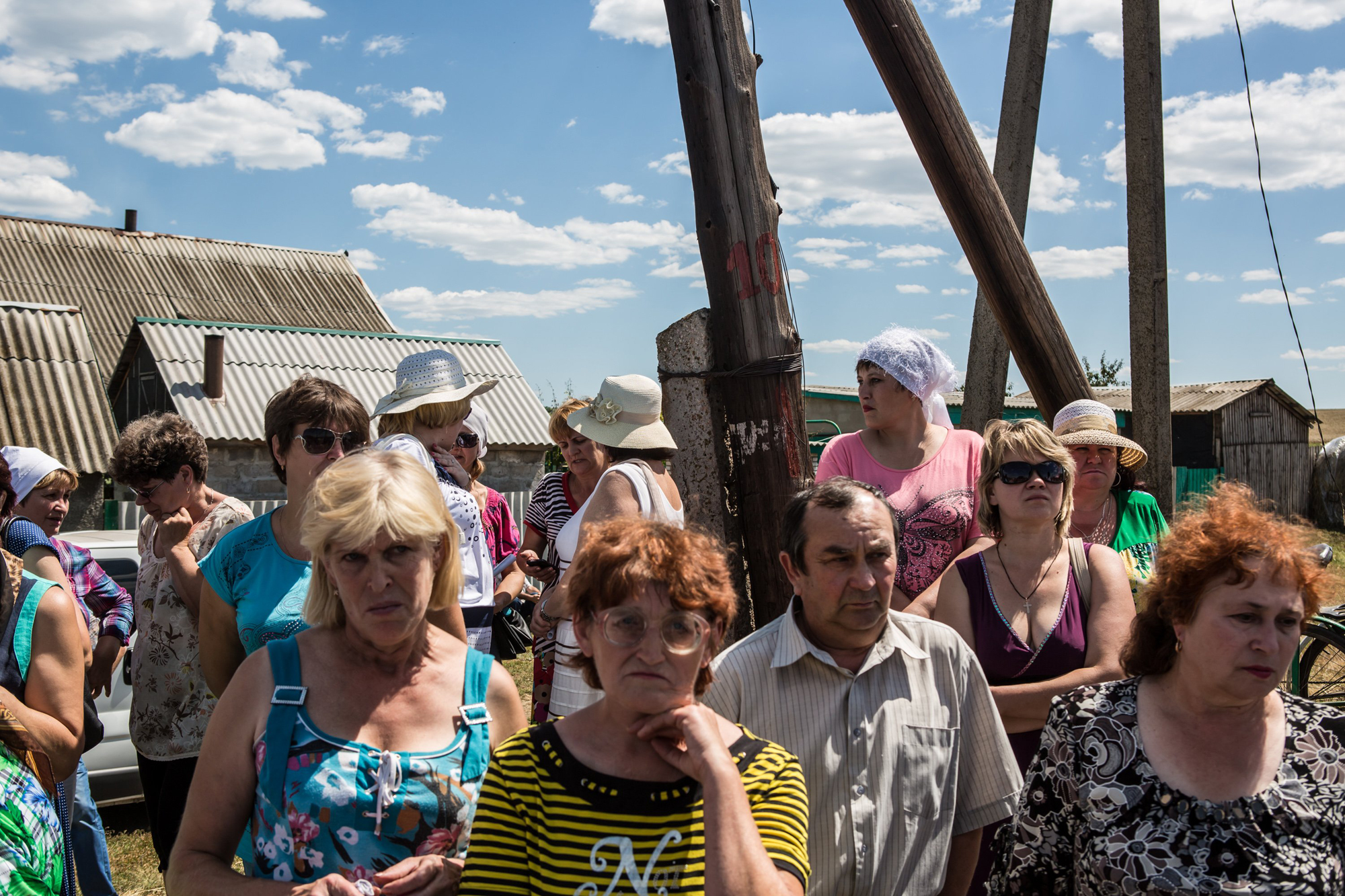 Local residents gather to watch as the bodies of victims of Malaysia Airlines Flight 17 are removed from the scene of the crash on July 21, 2014 in Grabovo, Ukraine.