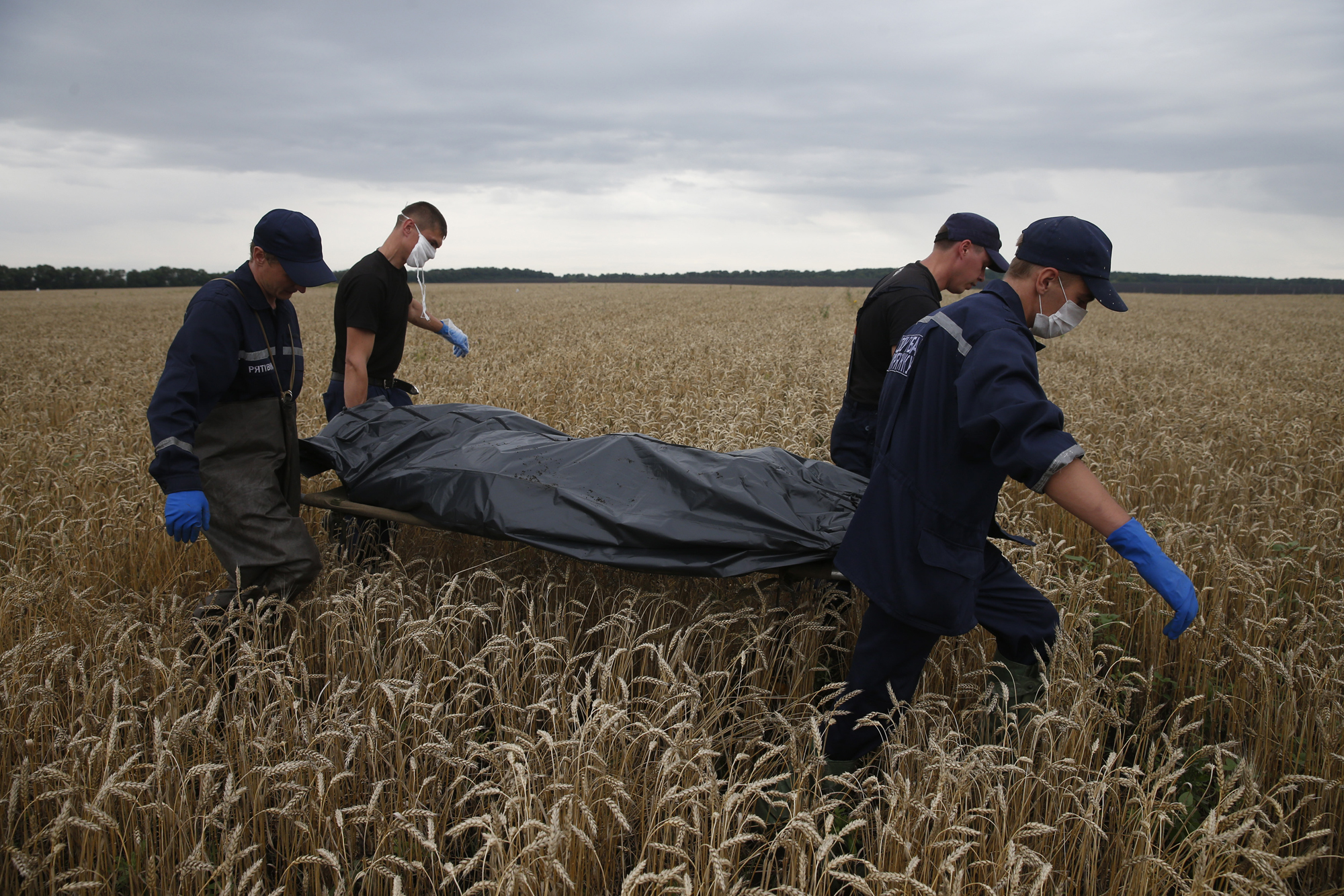 Emergency workers carry a body at the crash site of Malaysia Airlines Flight MH17, near the settlement of Grabovo in the Donetsk region, July 19, 2014.