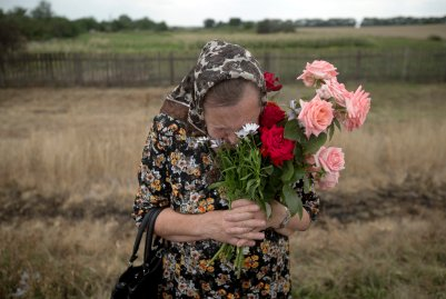 A woman cries during a religious service held by villagers in memory of the victims at the crash site of Malaysia Airlines Flight 17, near the village of Hrabove, eastern Ukraine, July 22, 2014.