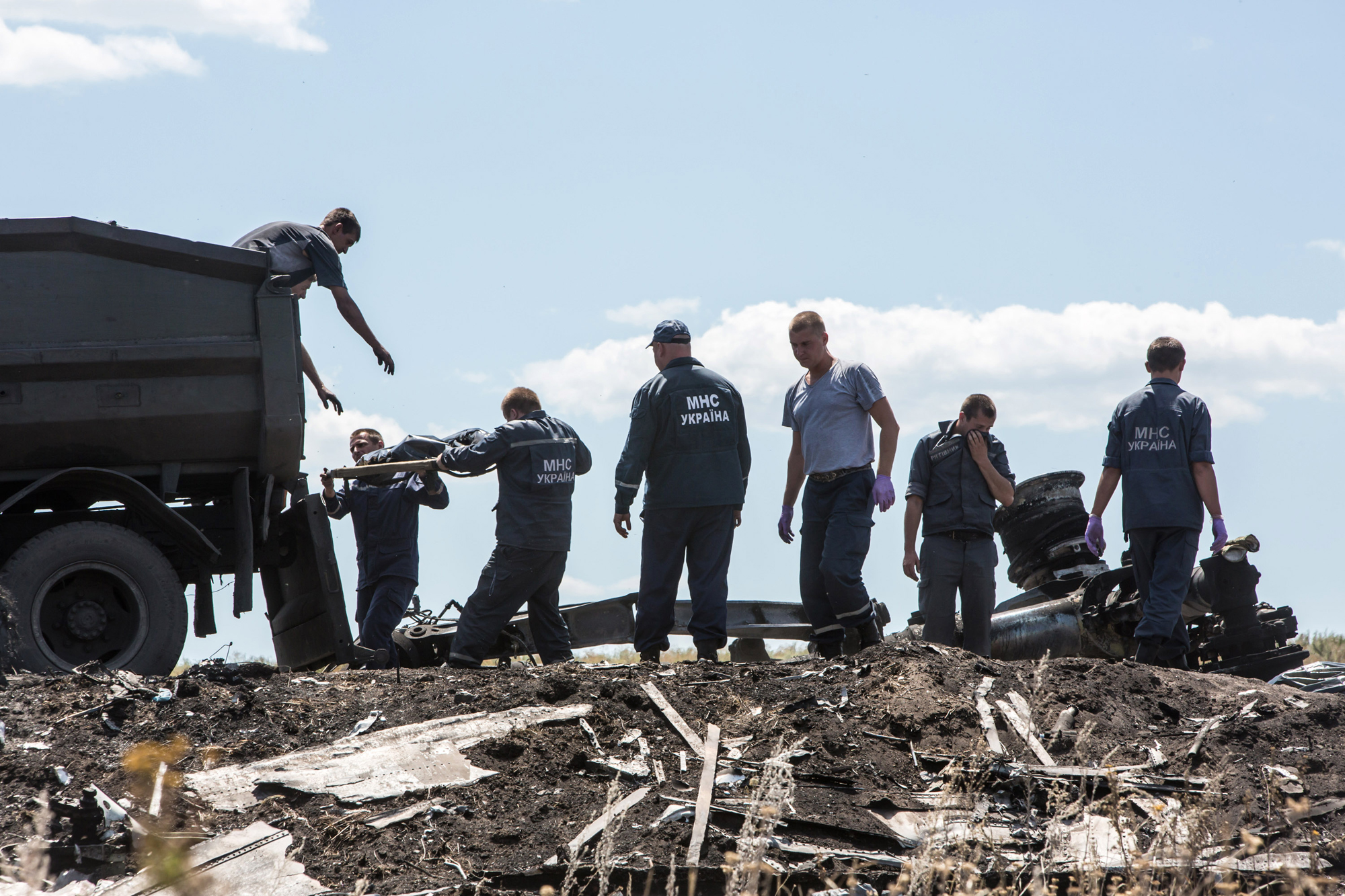 Personnel from the Ukrainian Emergencies Ministry load the bodies of victims of Malaysia Airlines flight MH17 into a truck at the crash site on July 21, 2014 in Grabovo, Ukraine.