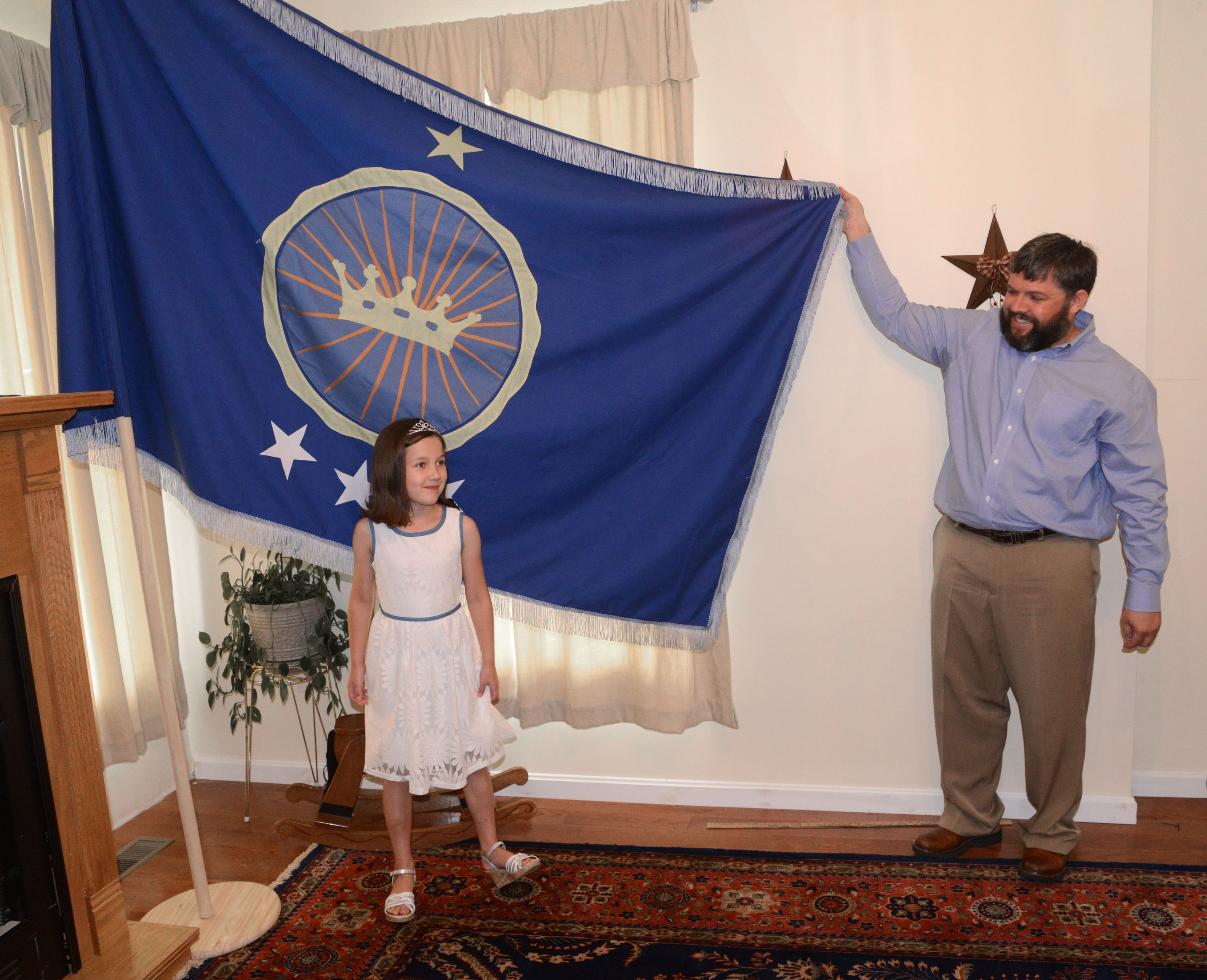 Jeremiah Heaton and his seven year-old daughter, Princess Emily, show the flag on July 2, 2014, in Abingdon, Virginia, that their family designed as they try to claim a piece of land in the Eastern African region of Bir Tawil.