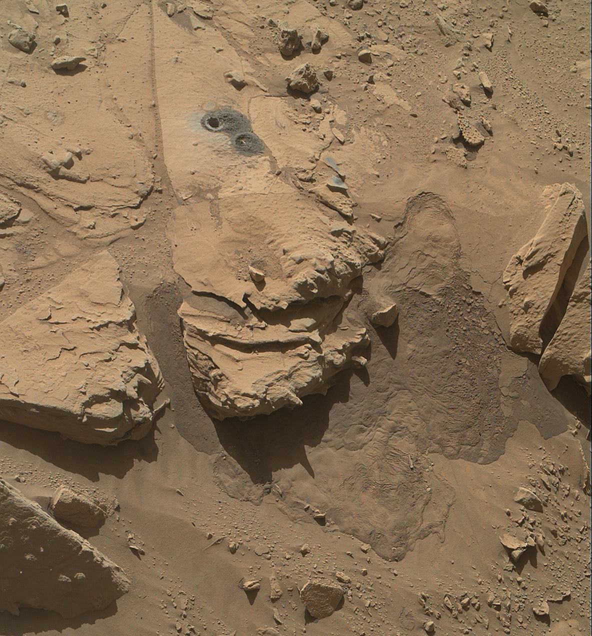 This view from the Mars Hand Lens Imager (MAHLI) on NASA's Curiosity Mars Rover shows the rock target  Windjana  and its immediate surroundings after inspection of the site by the rover.  The drilling of a test hole and a sample collection hole produced the mounds of drill cuttings that are markedly less red than the other visible surfaces. This view is from the 627th Martian day, or sol, of Curiosity's work on Mars (May 12, 2014).