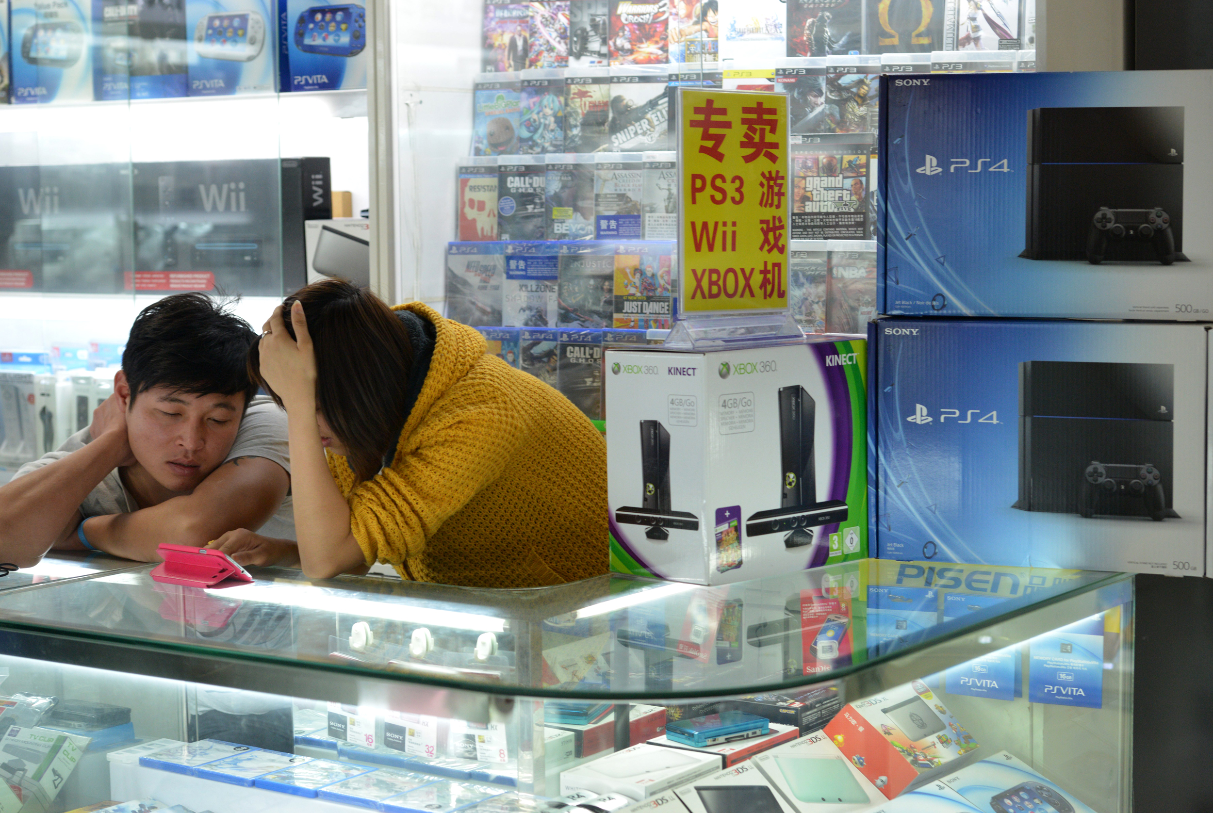 A vendor sells game consoles including Microsoft's Xbox One in a major electronics market in Shanghai on January 8, 2014.