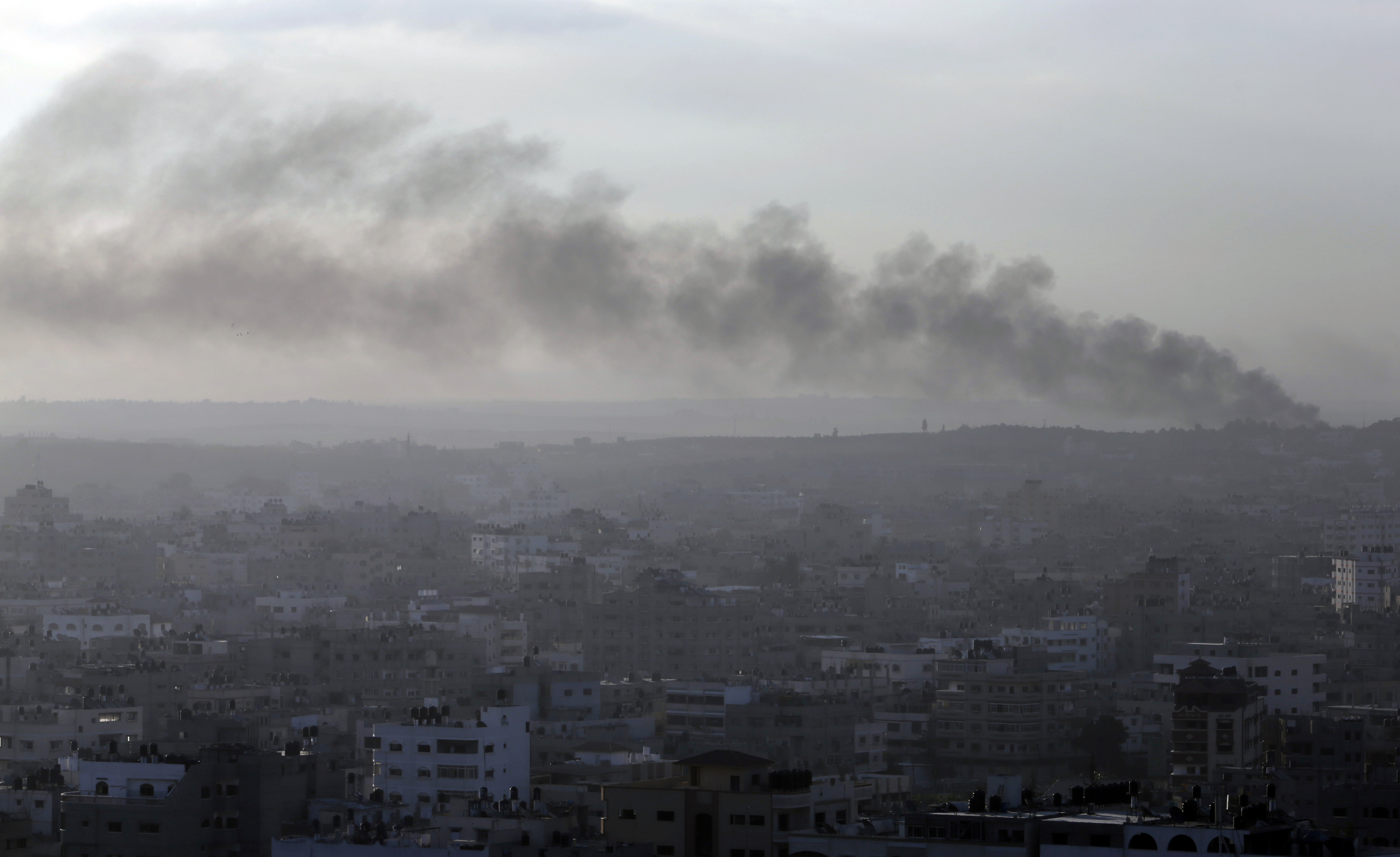 Amidst the morning fog, smoke from an Israeli strike rises over Gaza City on July 26, 2014