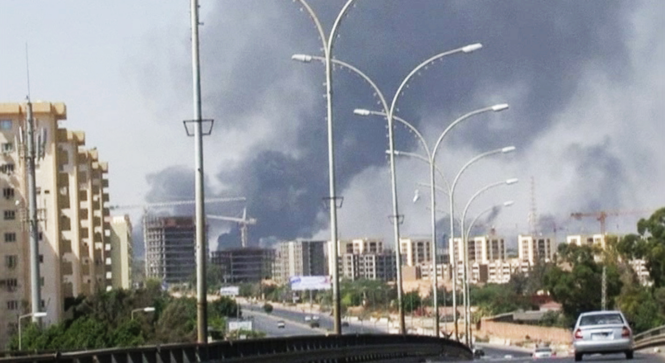 In this image made from video by the Associated Press, smoke rises from the direction of Tripoli International Airport, in the capital of Libya, on July 13, 2014