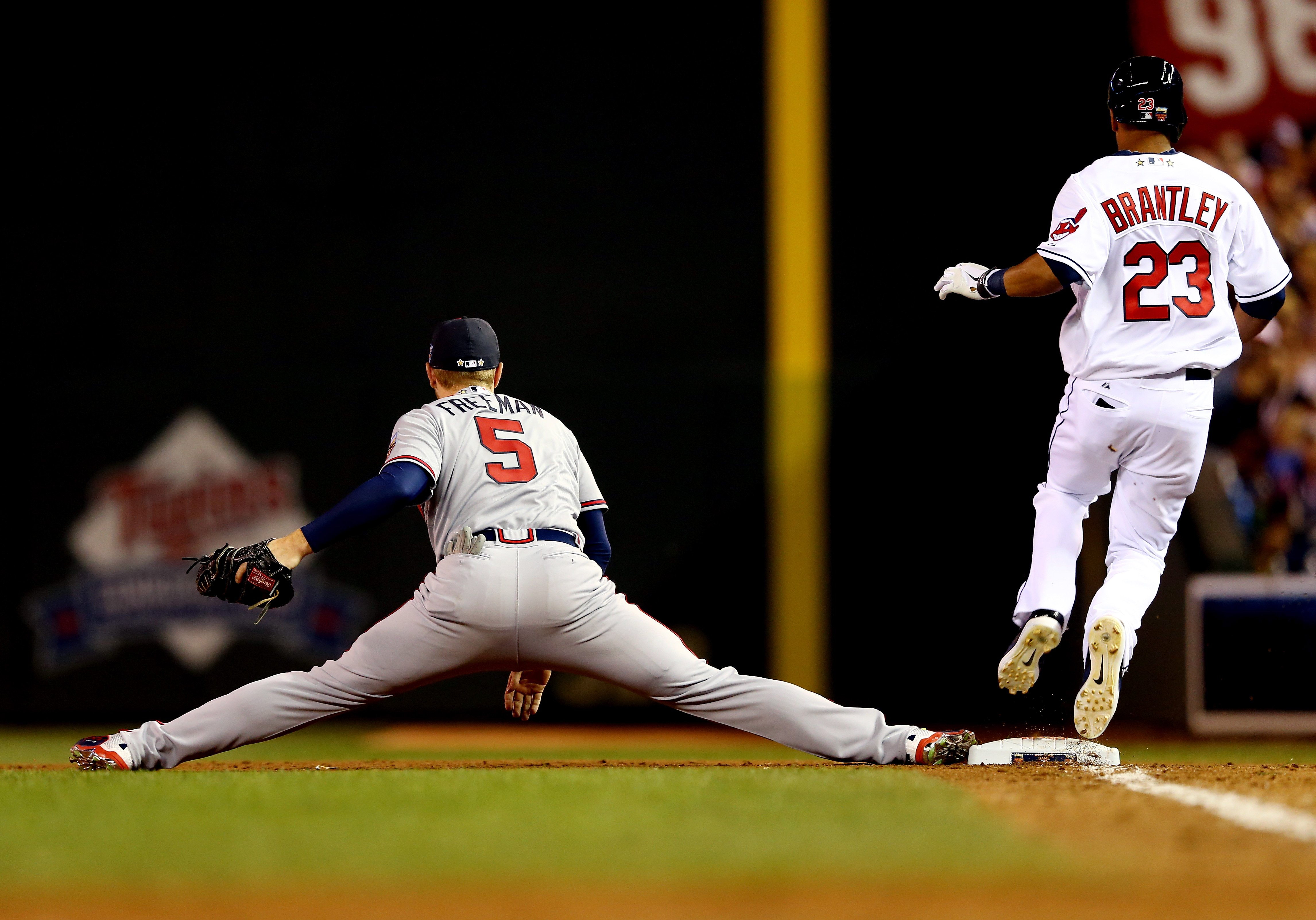 National League All-Star Freddie Freeman #5 of the Atlanta Braves stretches to make a catch as American League All-Star Michael Brantley #23 of the Cleveland Indians runs to first base during the 85th MLB All-Star Game at Target Field on July 15, 2014 in Minneapolis.
