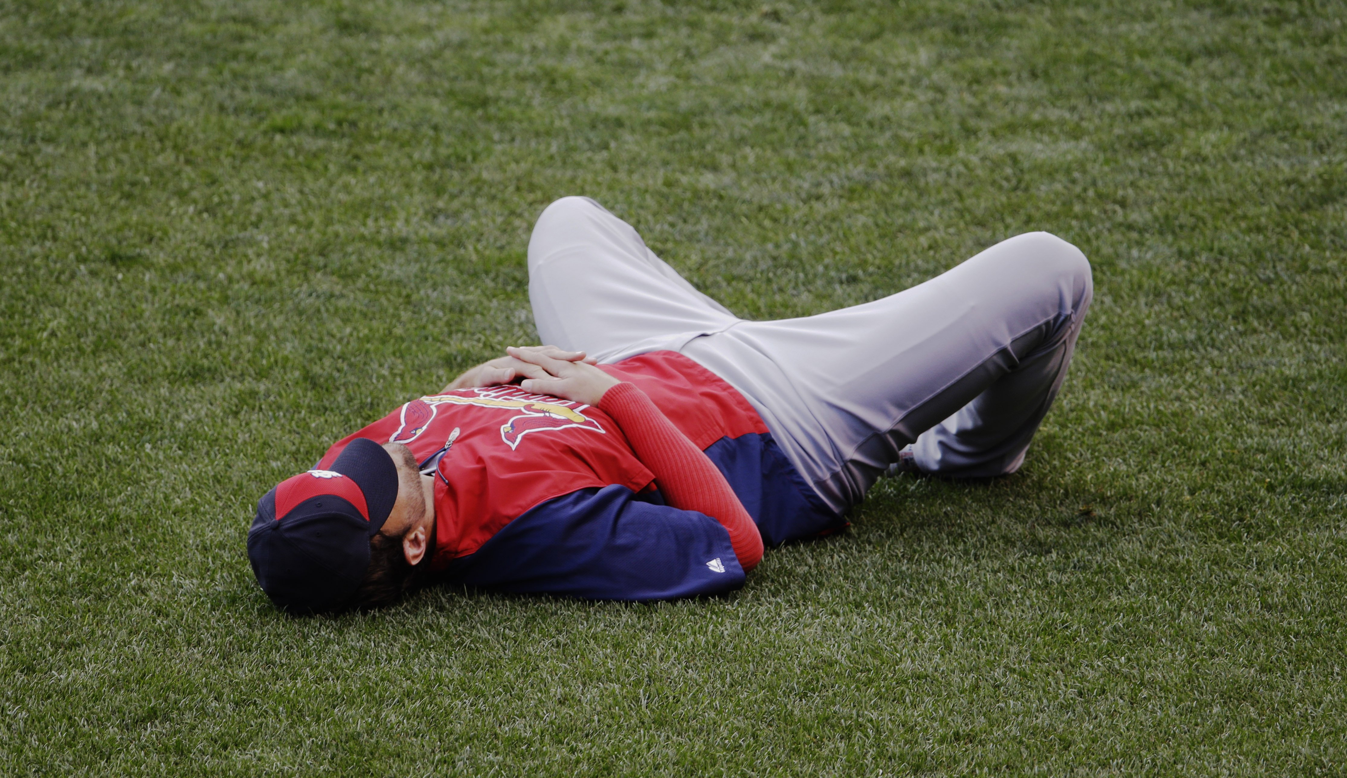 National League starting pitcher Adam Wainwright rests in the outfield before the MLB All-Star baseball game, Tuesday, July 15, 2014, in Minneapolis.