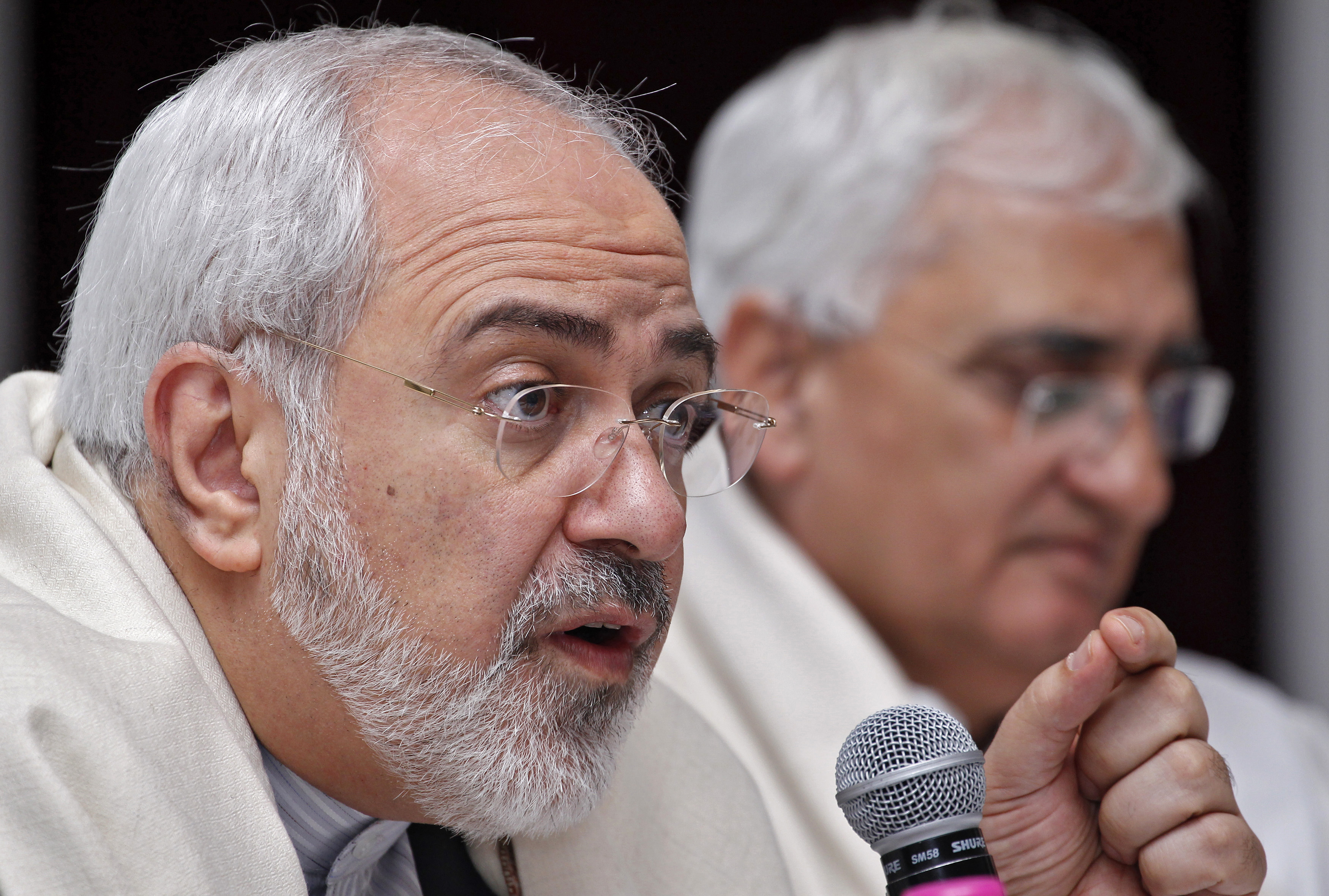 Iran's Foreign Minister Mohammad Javad Zarif speaks as his Indian counterpart Salman Khurshid watches during a lecture themed  Iran's Foreign Policy - Towards Stability in West Asia  organized by the Observer Research Foundation in New Delhi on February 27, 2014.