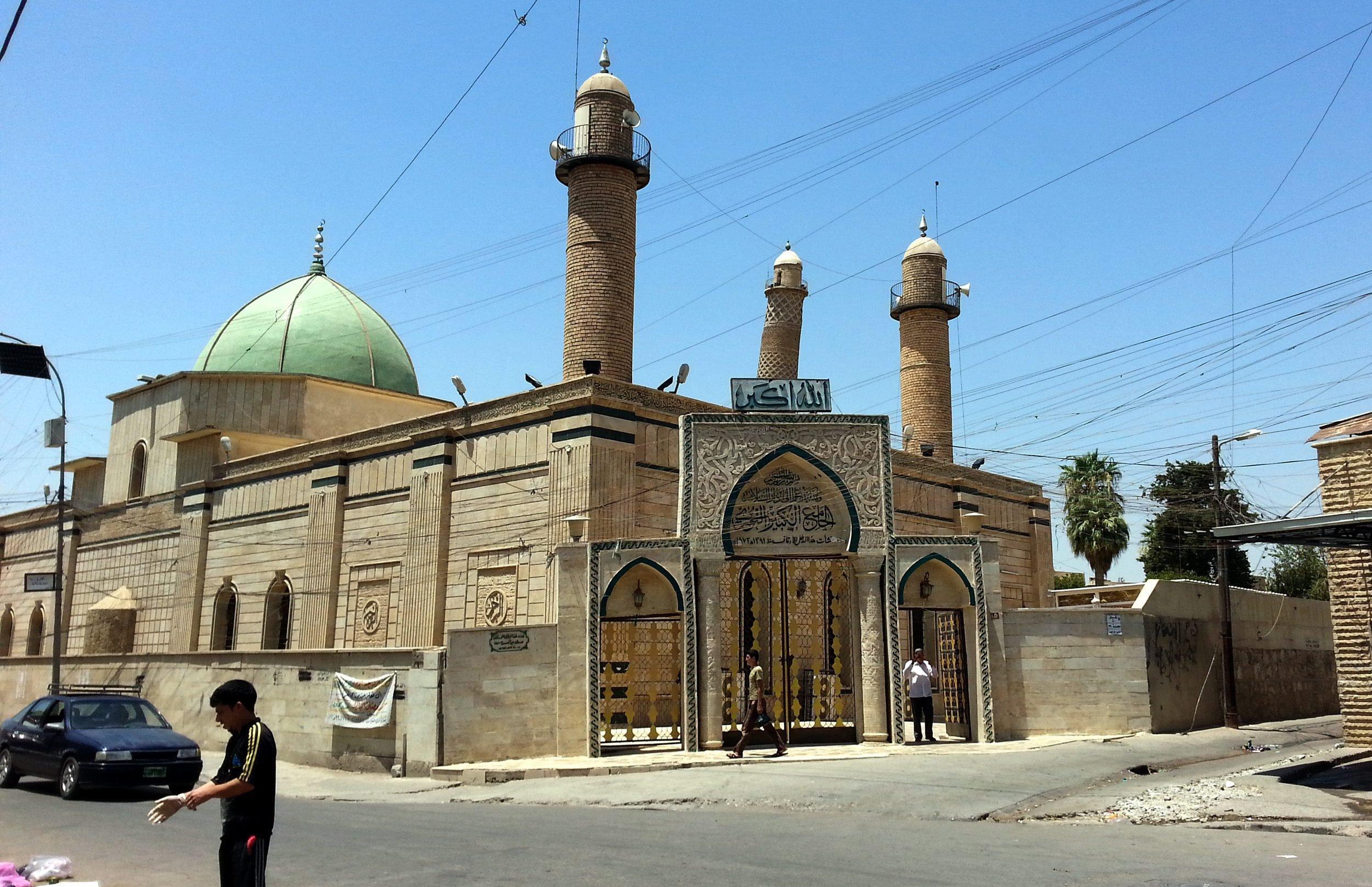 Iraqis walk next to the Al-Noori Al-Kabeer mosque in Mosul city, northern Iraq on July 9, 2014.