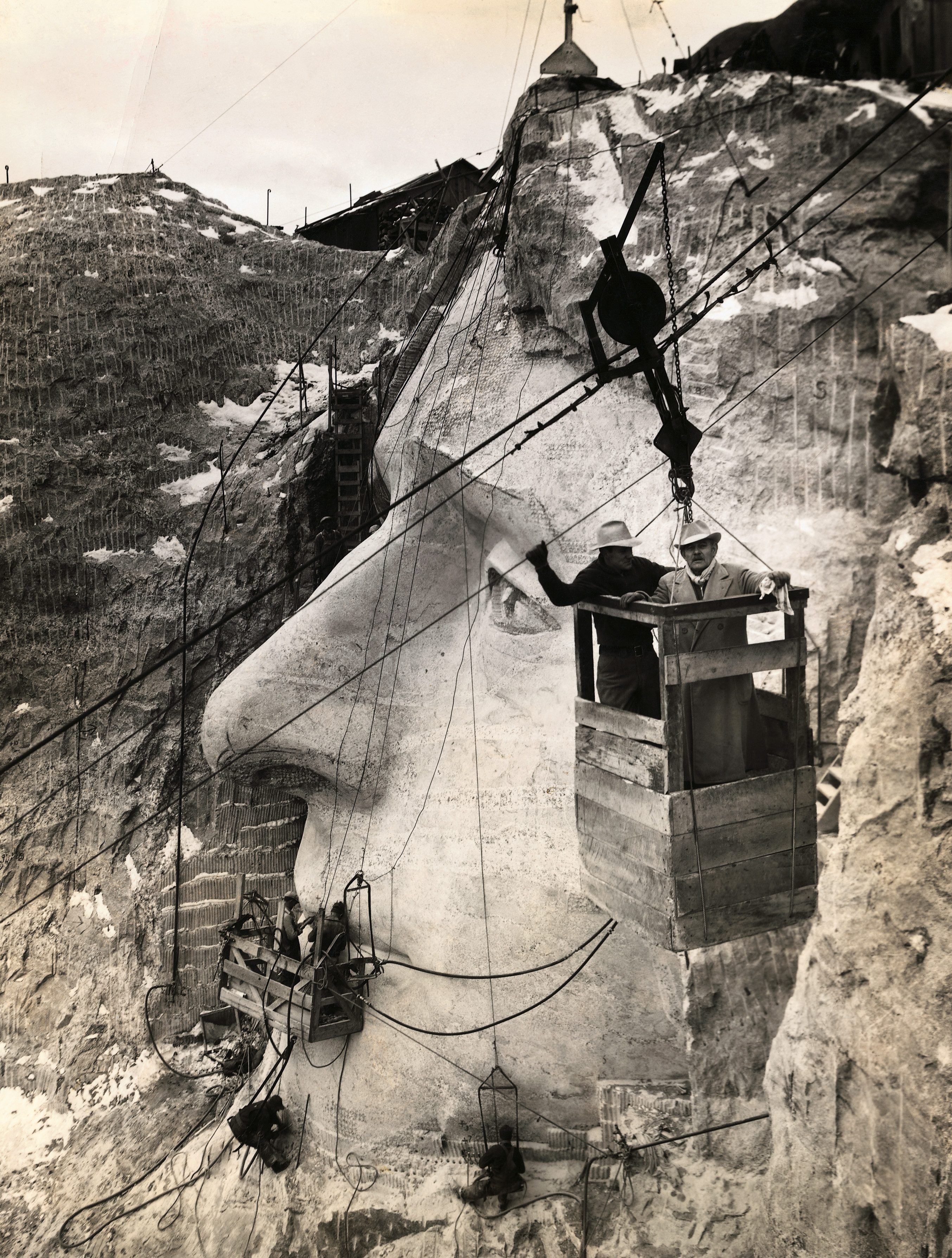 American sculptor Gutzon Borglum and his son, Lincoln, inspect the Jefferson head from an aerial tram in the Black Hills area of Keystone, S.D. on Nov. 23, 1935.