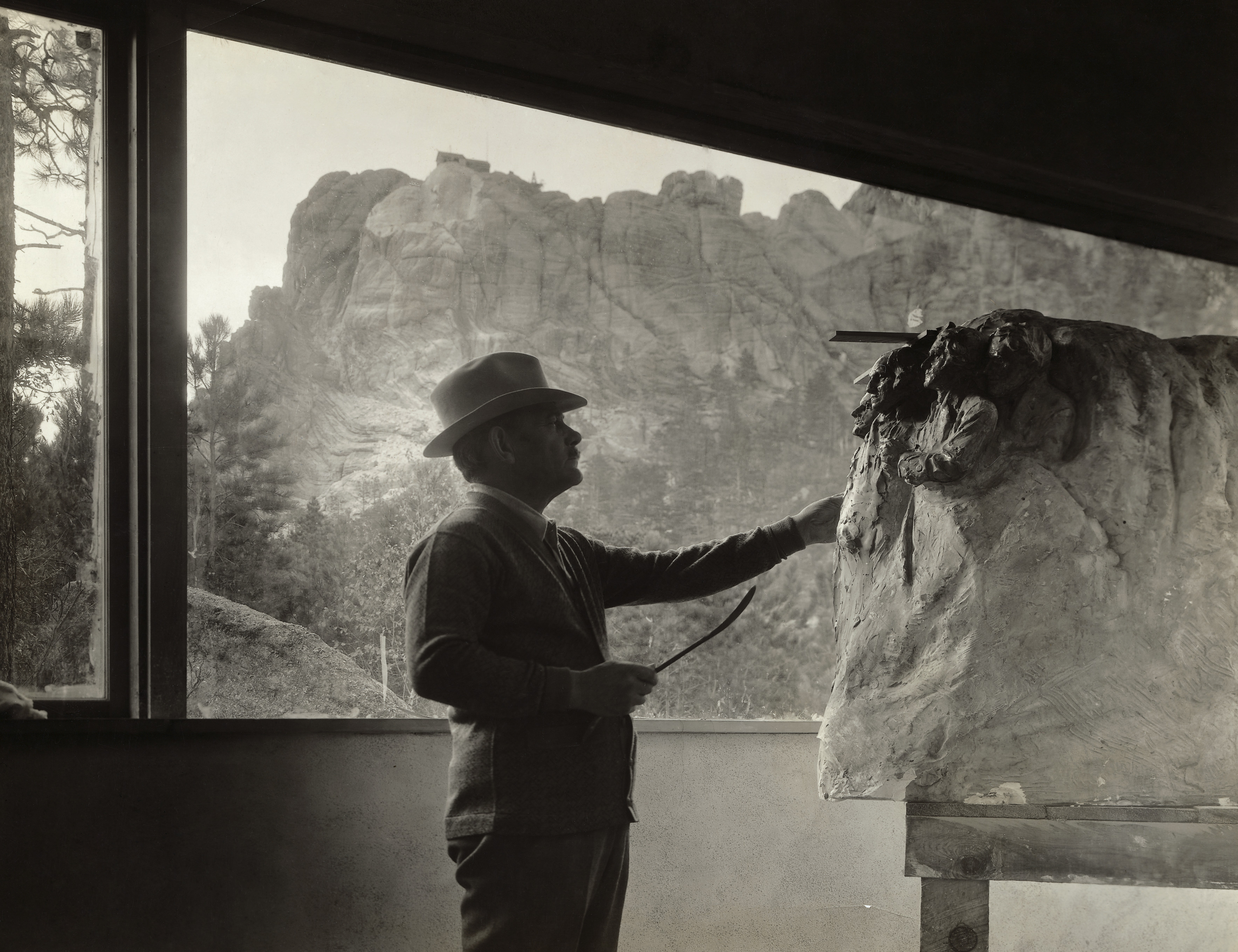 Gutzon Borglum, American sculptor, at work on the model for Mount Rushmore in his studio near the Black Hills area of Keystone, S.D. circa 1930s.