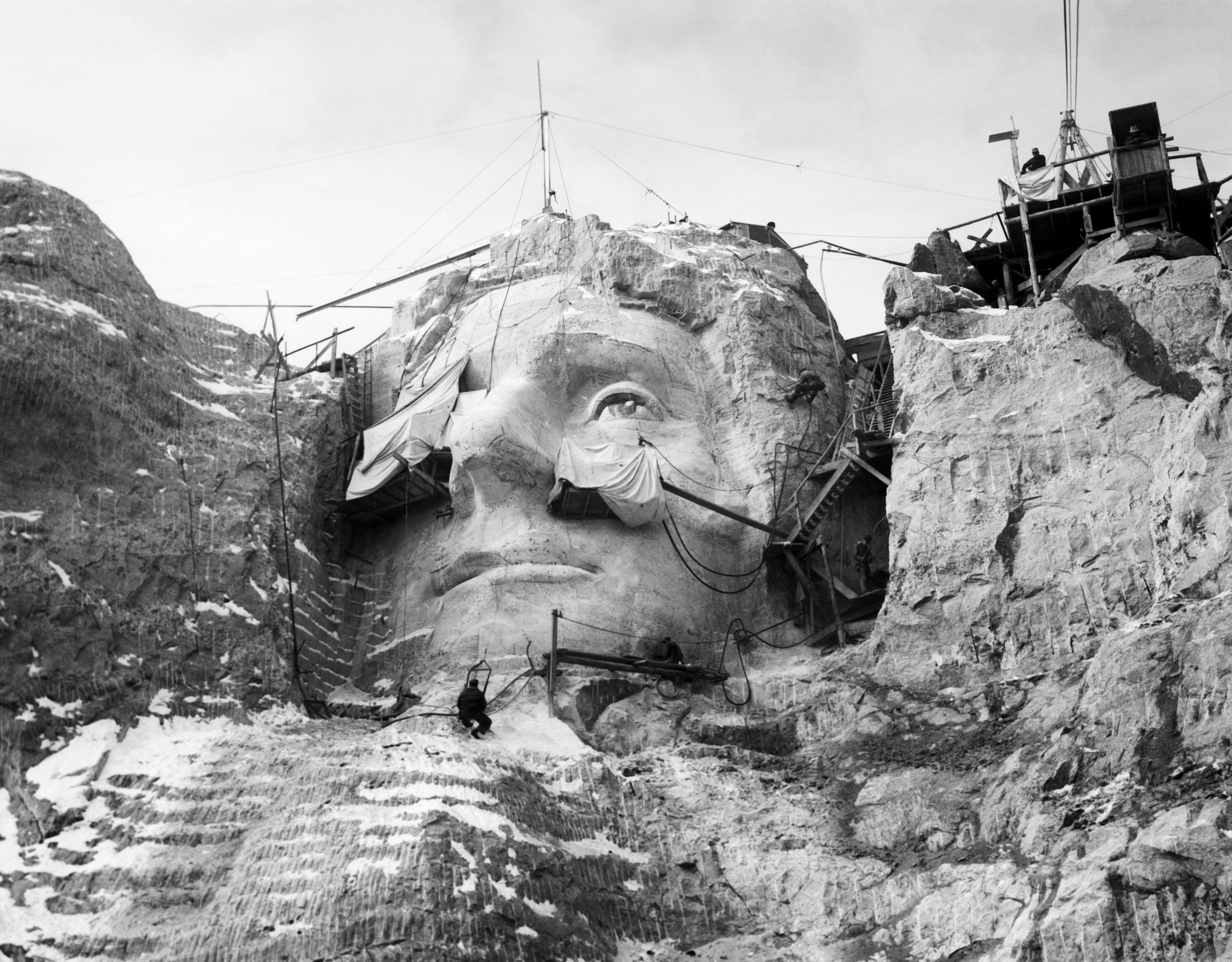Stone carvers on scaffolding carve the face of Thomas Jefferson into Mount Rushmore in the Black Hills area of Keystone, S.D. in 1930.