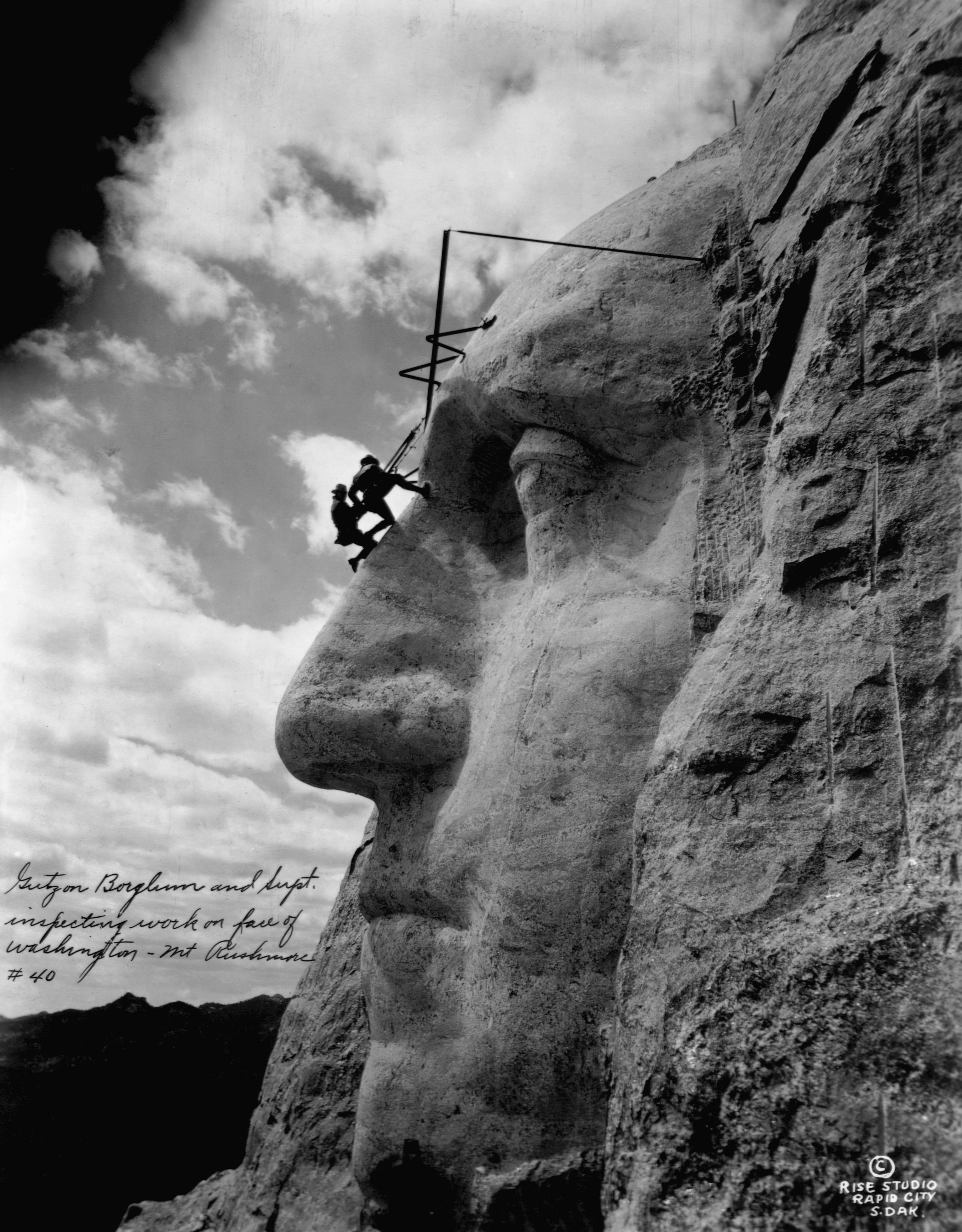 Gutzon Borglum and another man hang from the sculpted forehead of President George Washington on Borglum's famous monumental sculpture at Mount Rushmore in the Black Hills area of Keystone, S.D. on May 31, 1932.