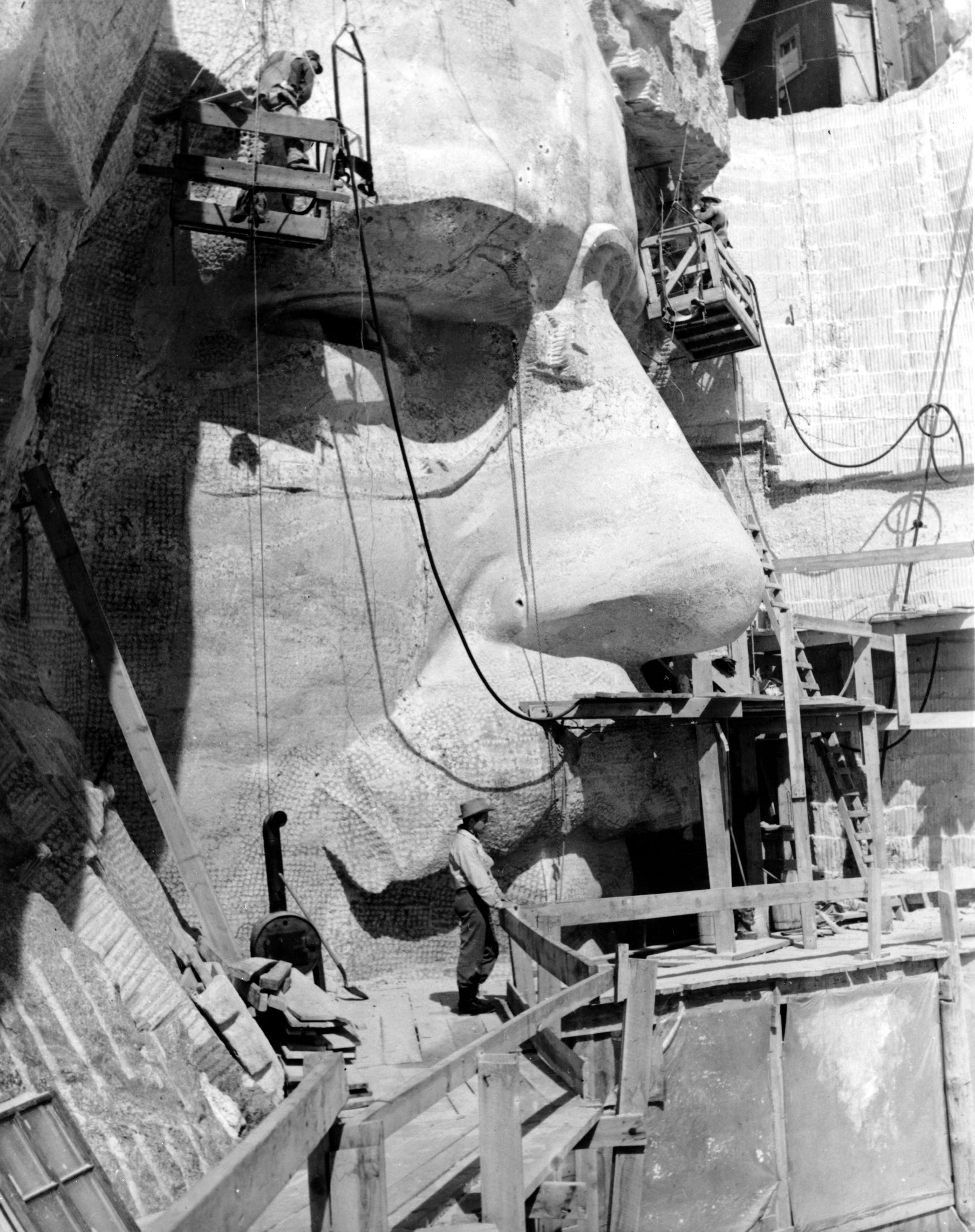 Sculptor Lincoln Borglum on the scaffold below the stone face of U.S. President Theodore Roosevelt on the Mount Rushmore Memorial in the Black Hills area of Keystone, S.D., April, 1944.